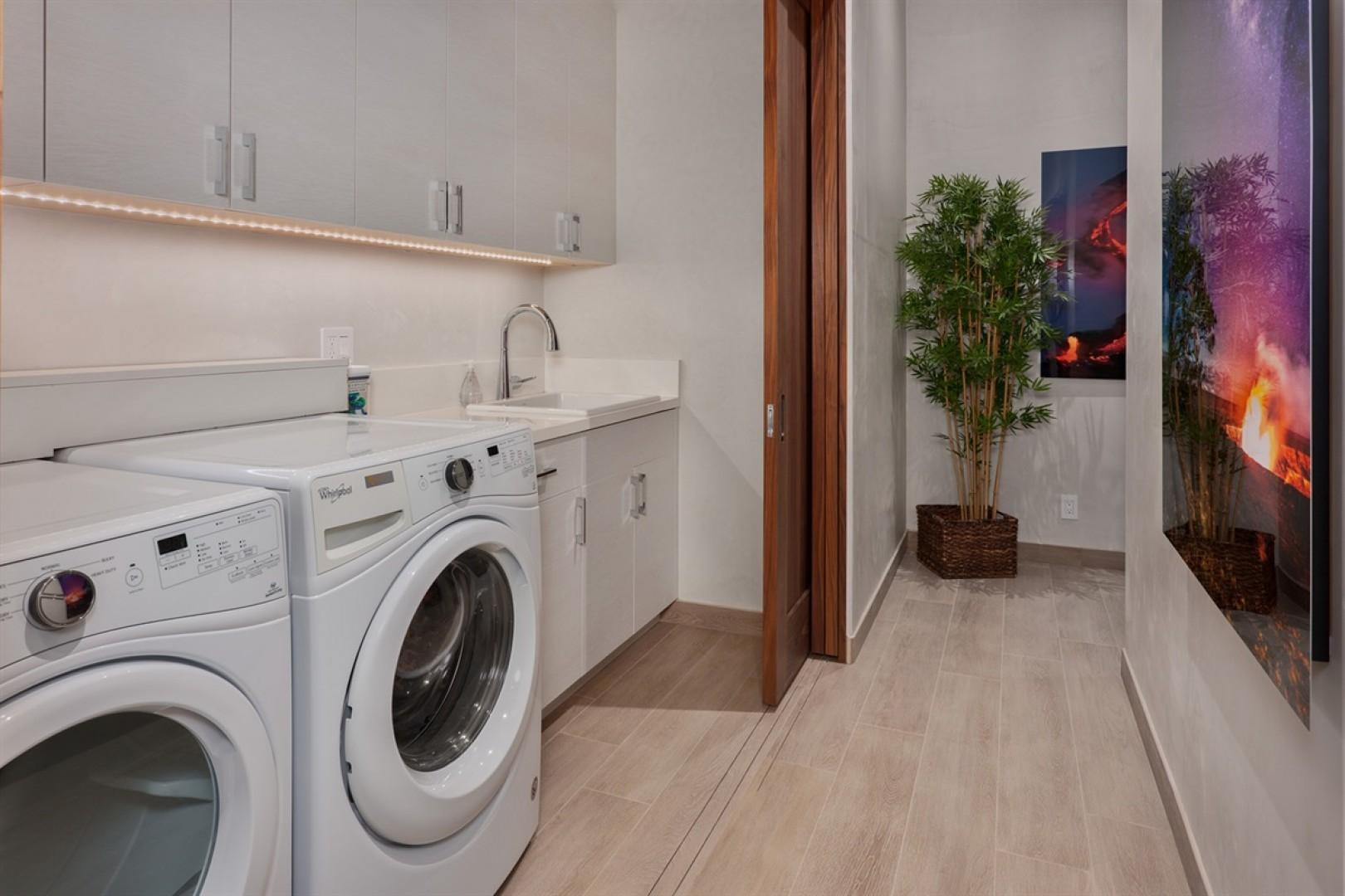 Dedicated laundry area inside the home with oversized washer and dryer and sink.