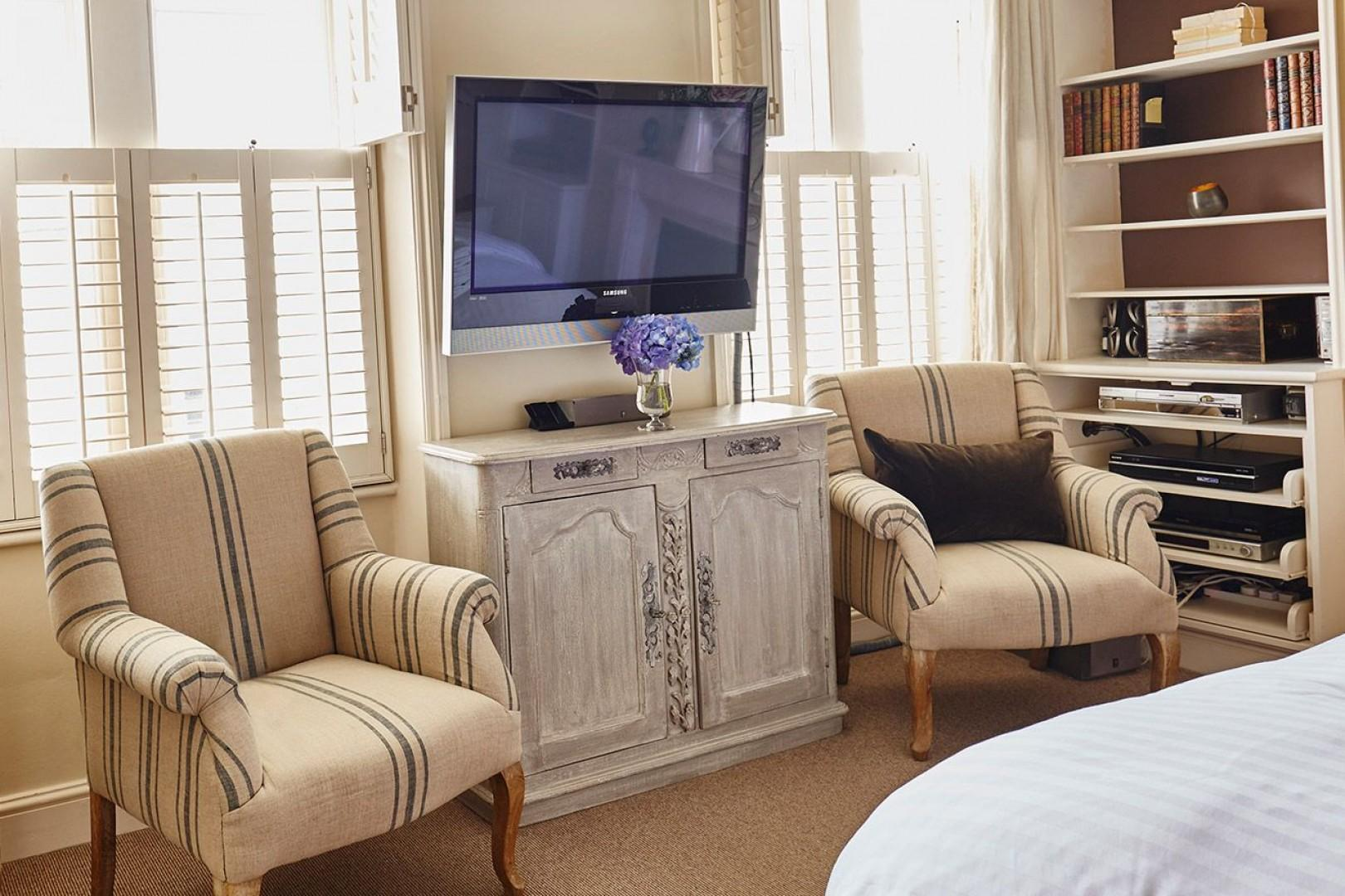 Flat screen TV and two armchairs in the first bedroom