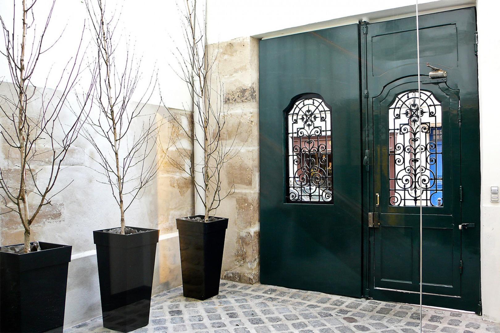 Enter through old wooden doors to a cobblestone courtyard.