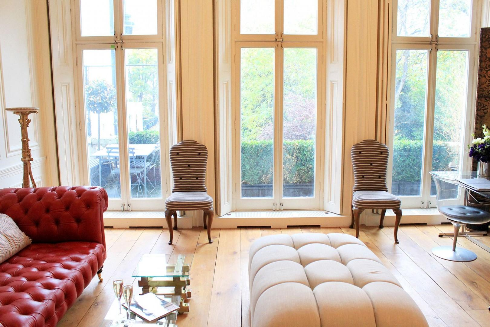 Large French doors open to an inviting balcony with table and chairs