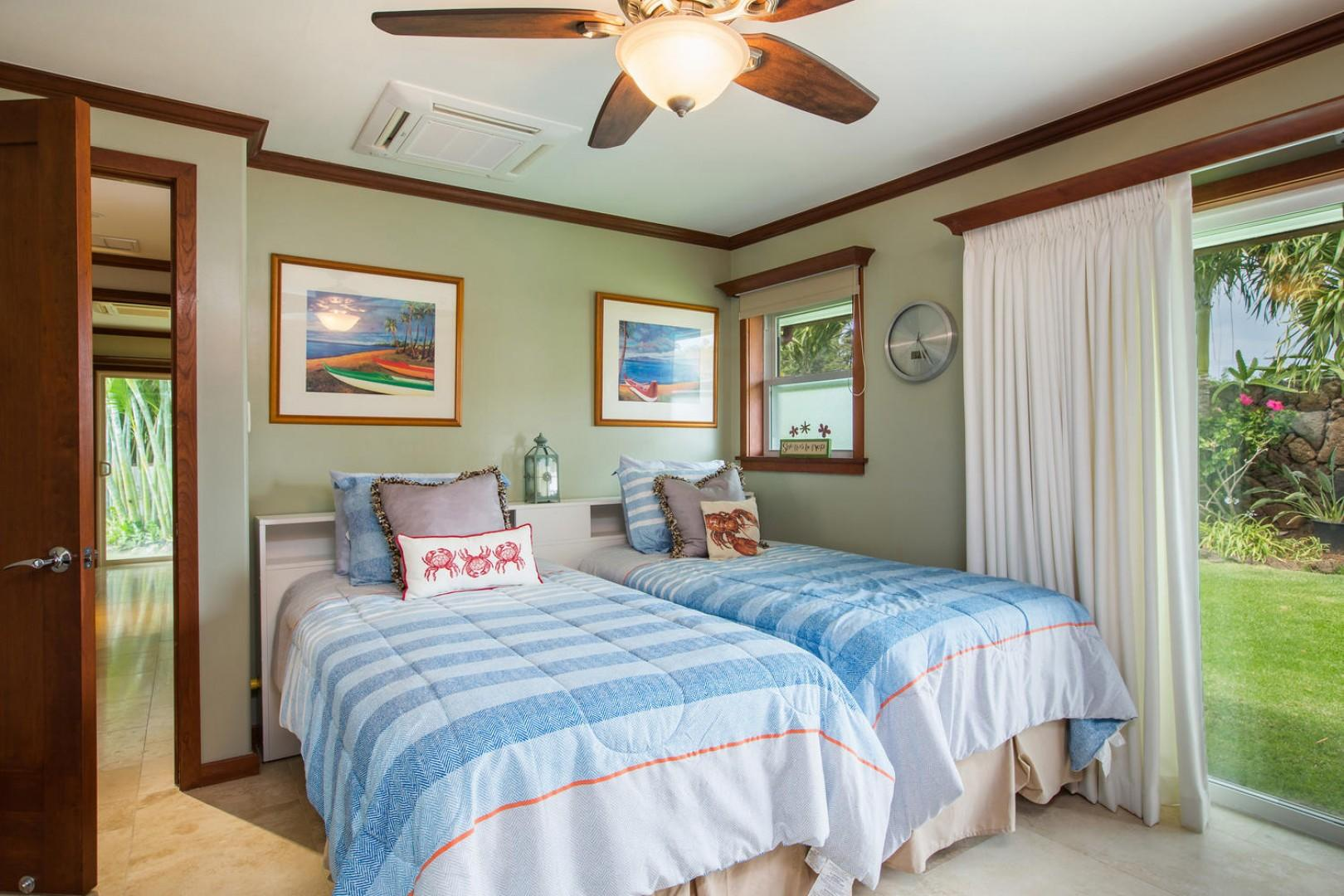 The twin bedroom with a television and sliding door to the lawn.