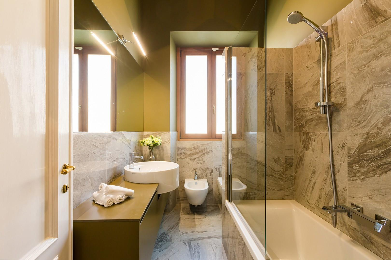 Luxurious bathroom 1 gets lots of light. Sink has excellent counter top space.