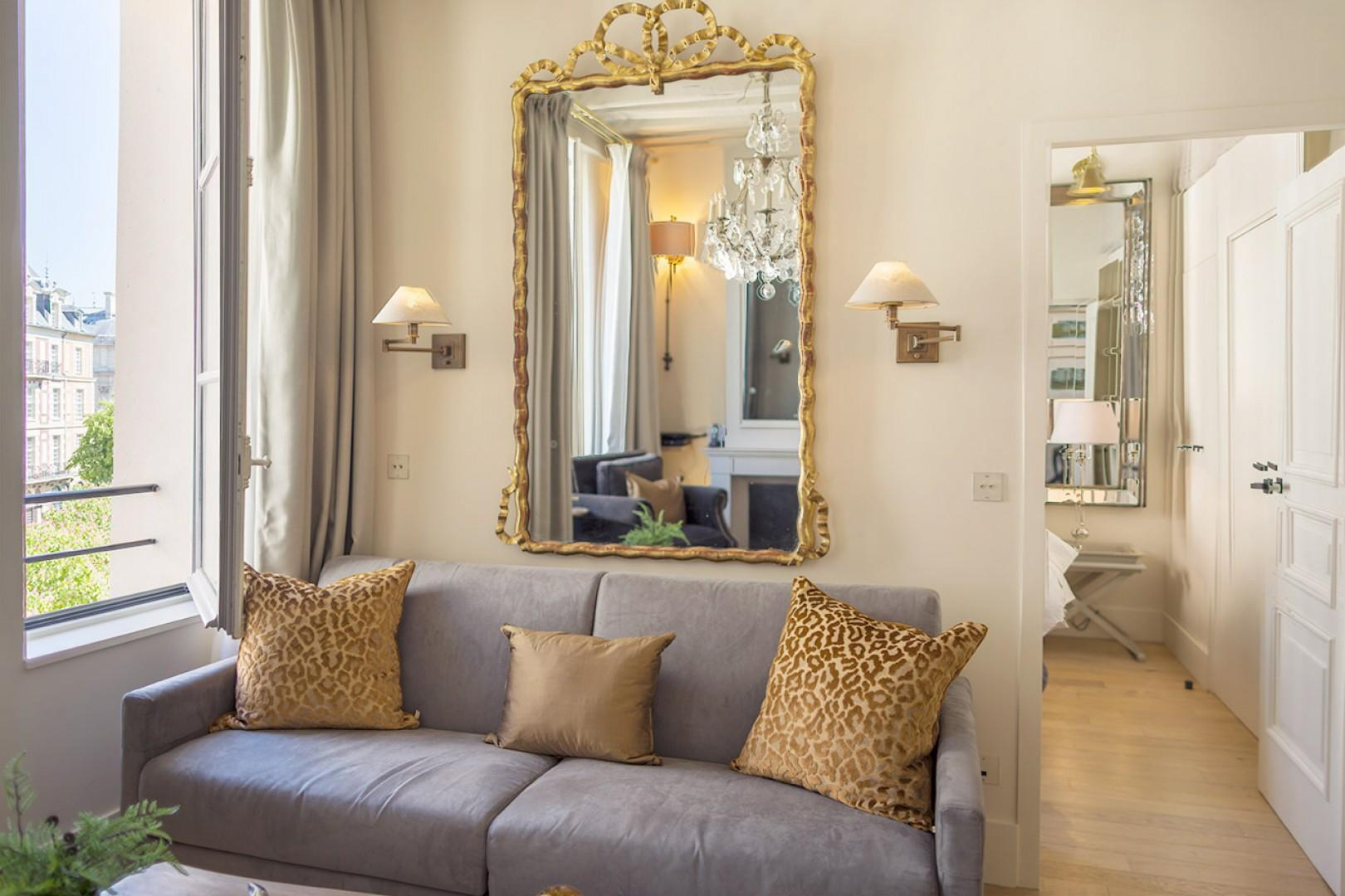 Enjoy views of Place Dauphine from the elegant sofa.