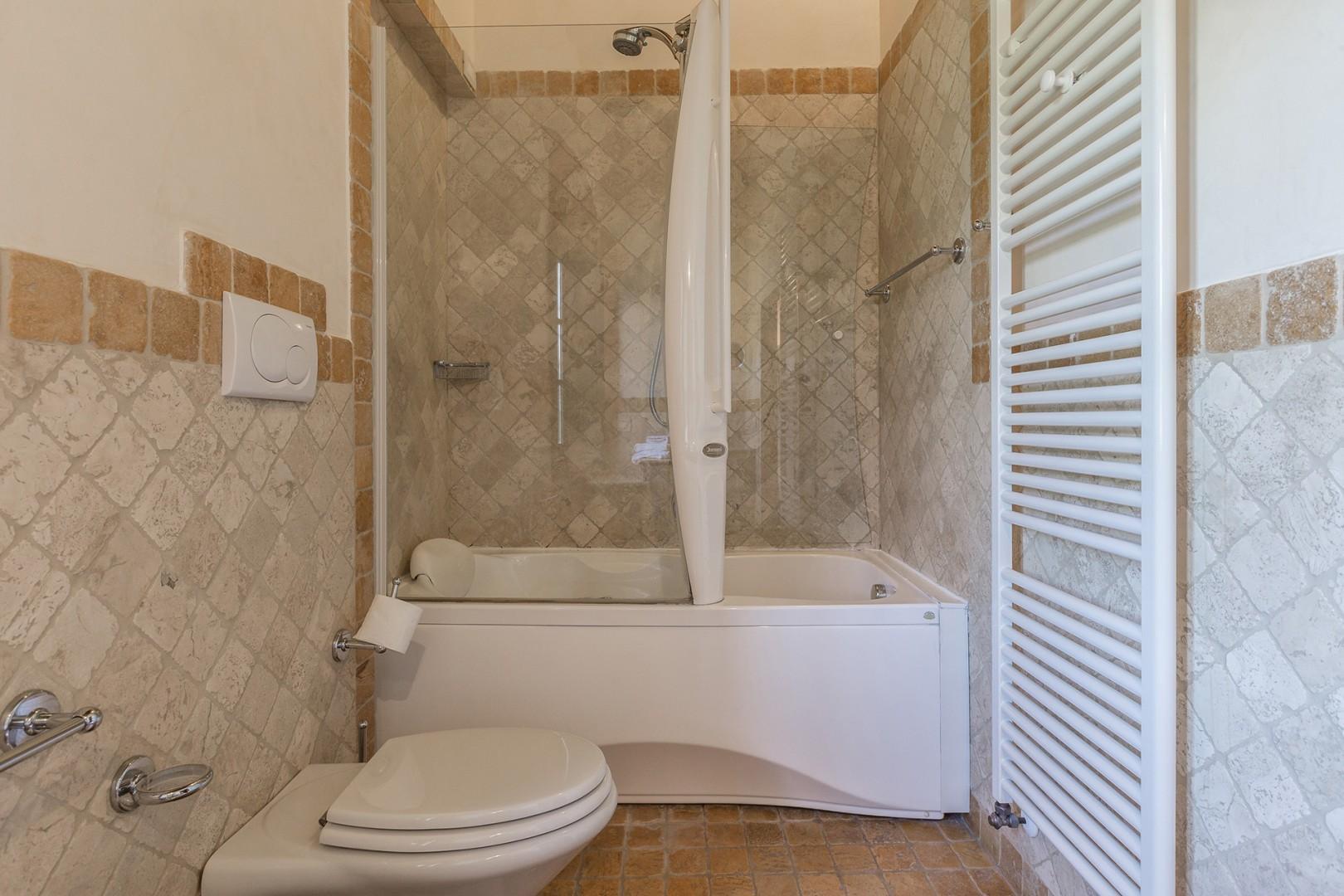 En suite bathroom to bedroom 1 features a jacuzzi bathtub and shower.