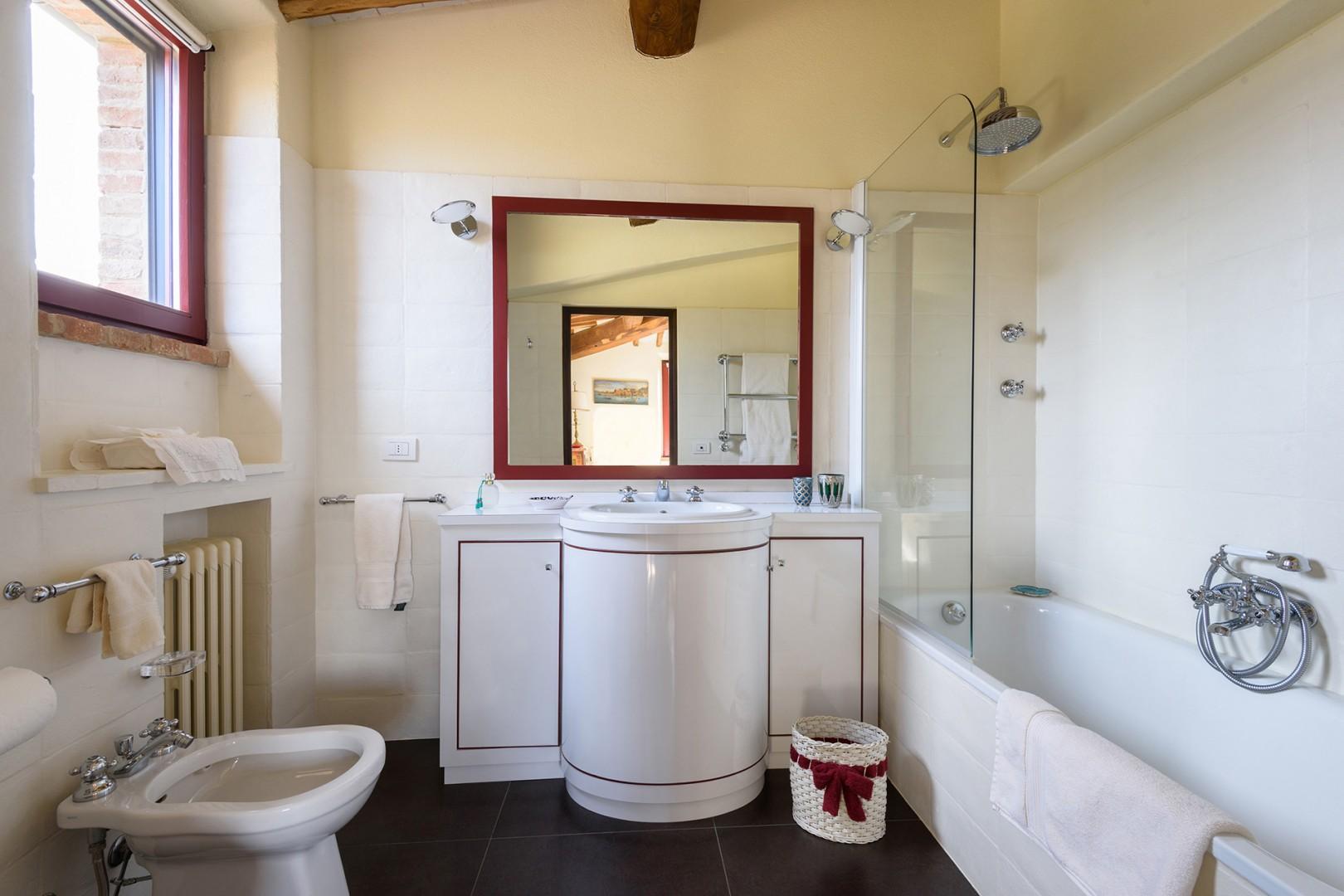 Bathroom with combination bathtub/shower and rainfall showerhead.