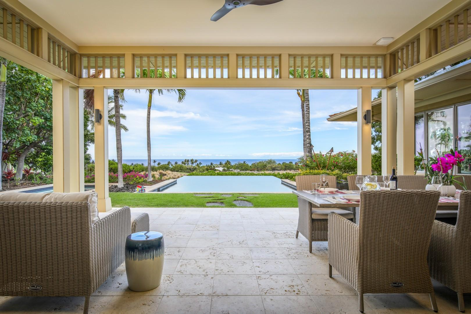 View of the pool deck and grassy lawn from the ample covered lanai.
