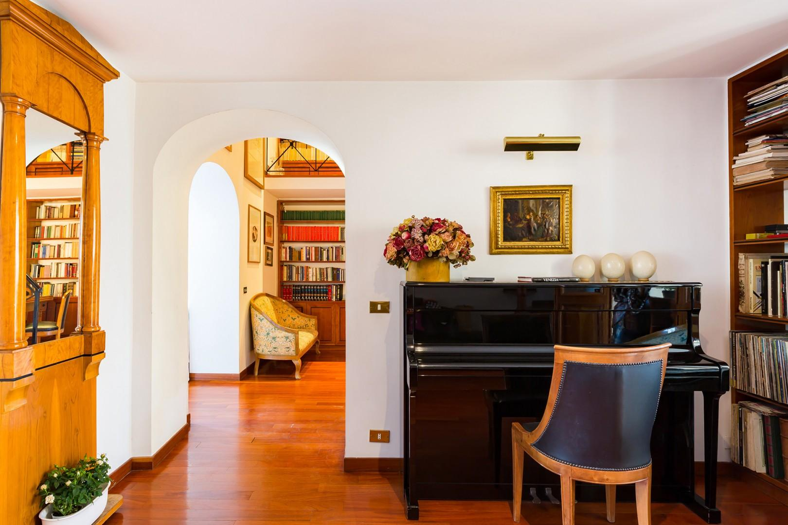 Foyer has a piano. The archway leads to the dining room.