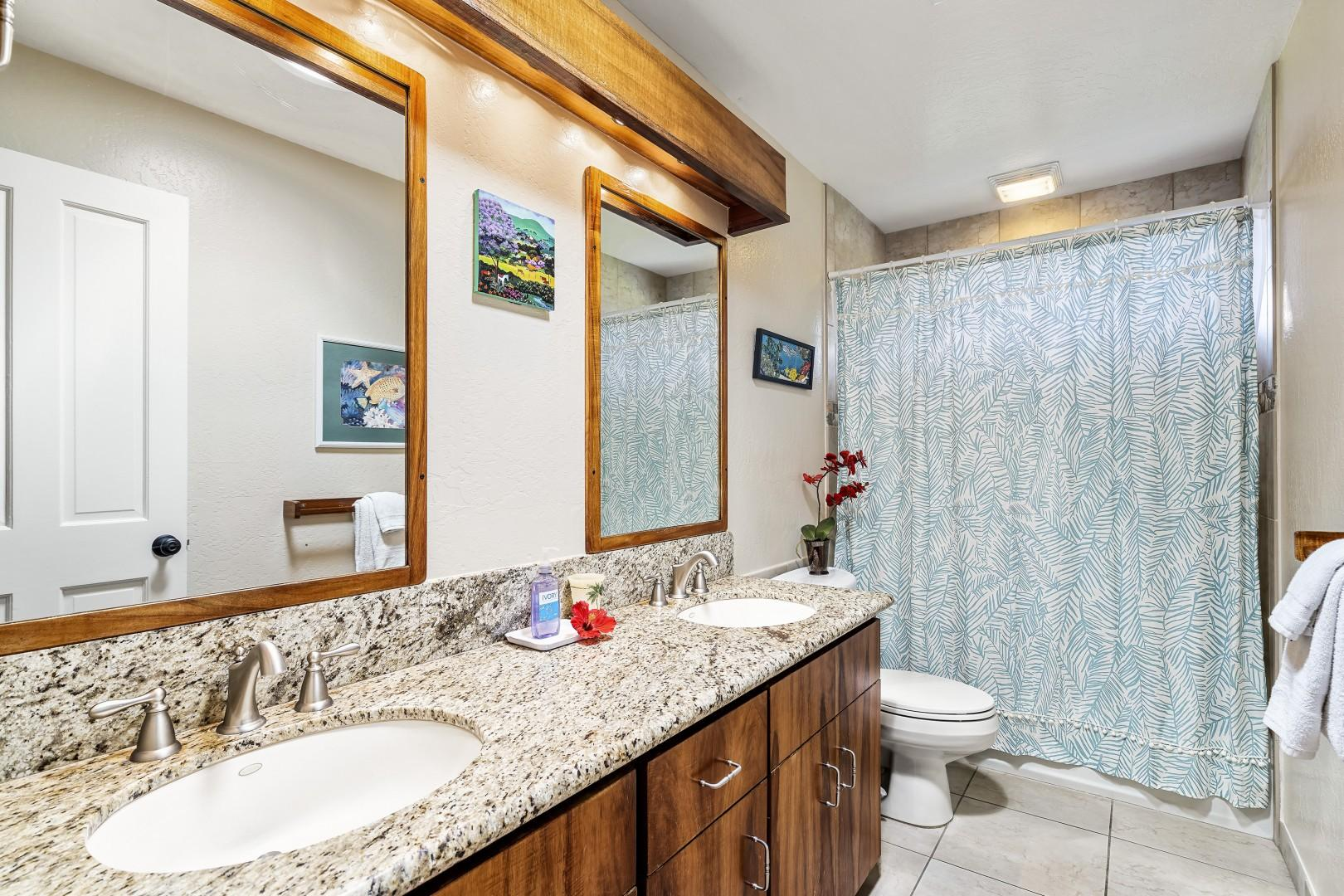 Guest bathroom equipped with dual vanities and shower/tub combo