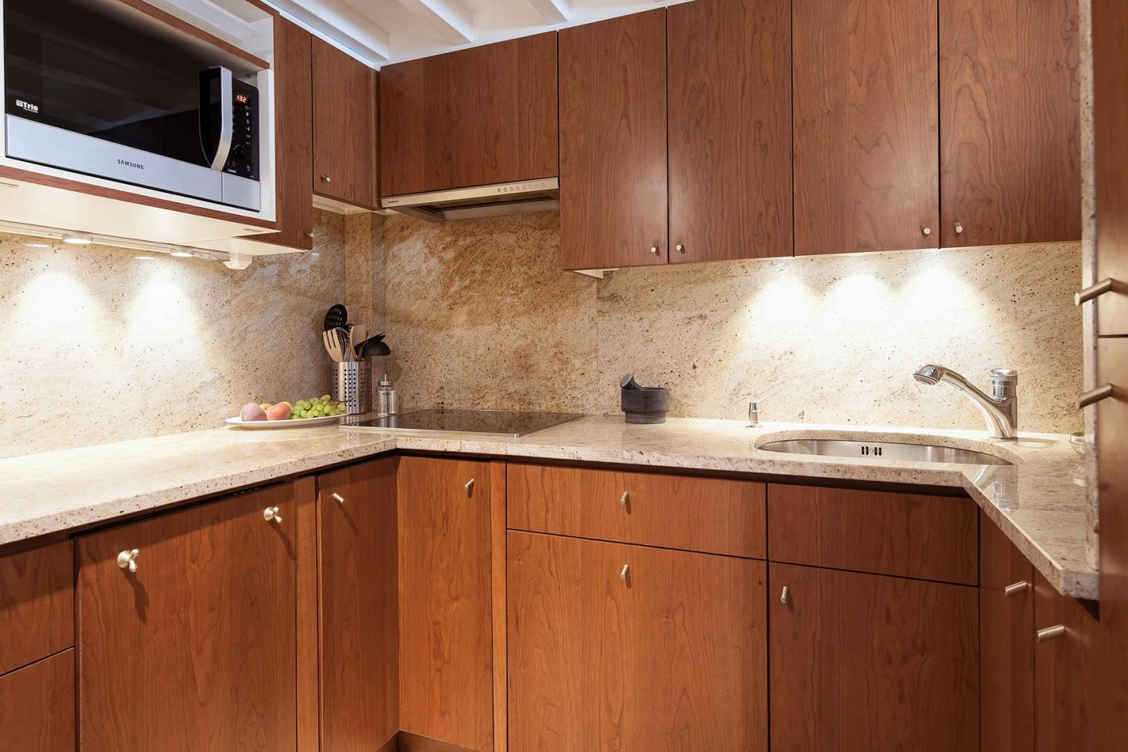 The fully-equipped kitchen is covered in marble and rich hardwood.