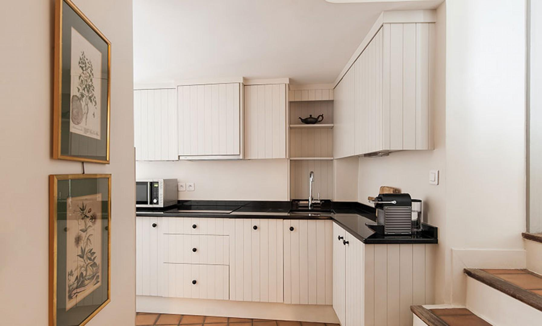 Steps lead down to the stylish black and white kitchen.