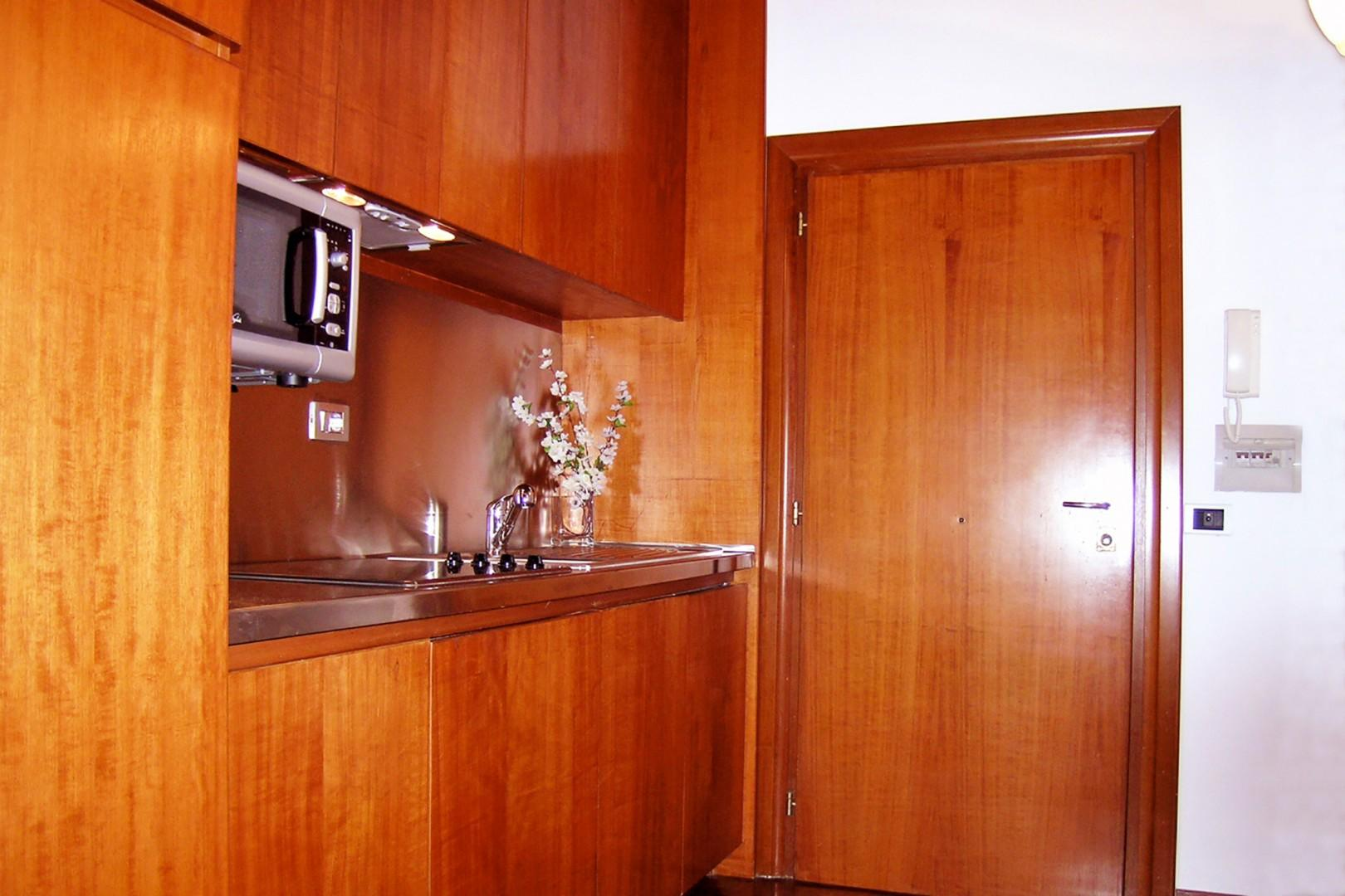 Enter the apartment front door and the kitchenette is immediately to your right.