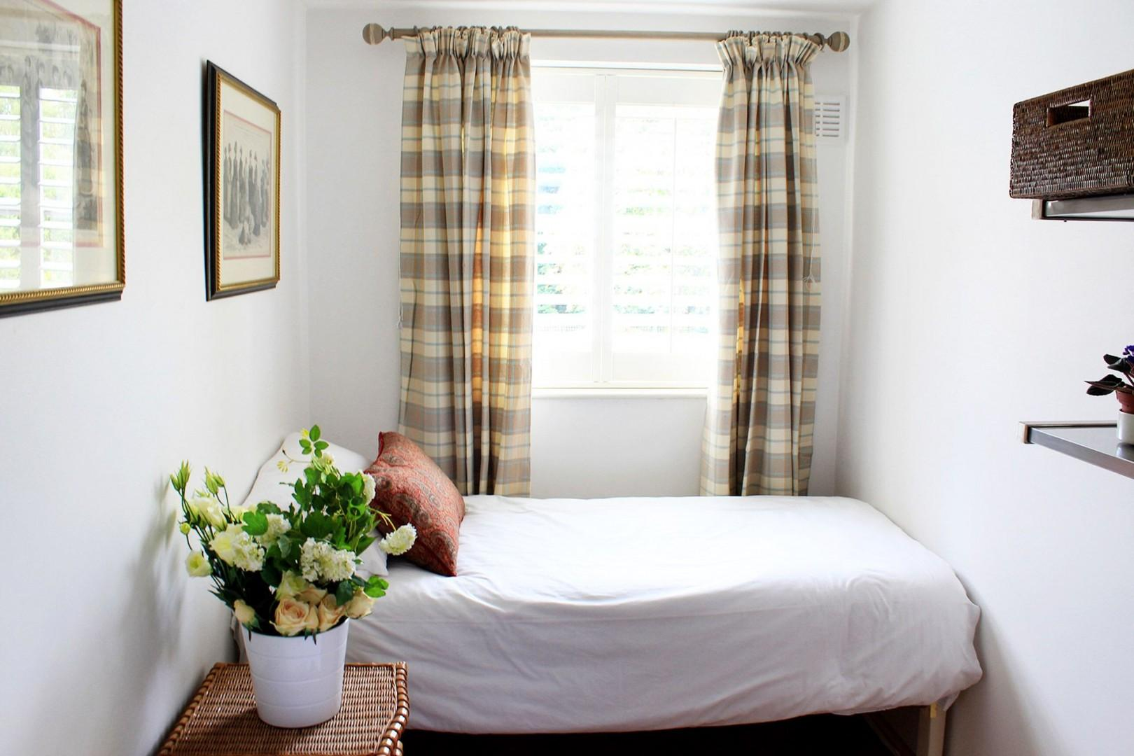 Sunny second bedroom features a comfortable bed and trundle
