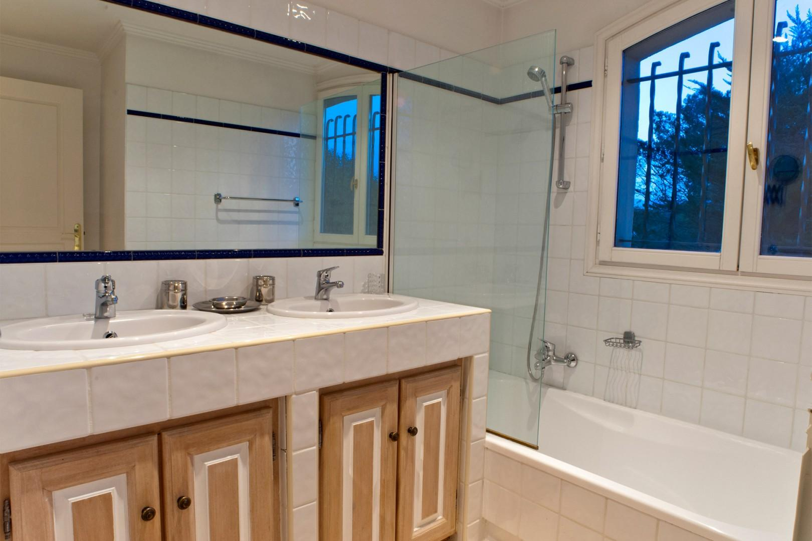 Bathroom three with bathtub with shower and double sink