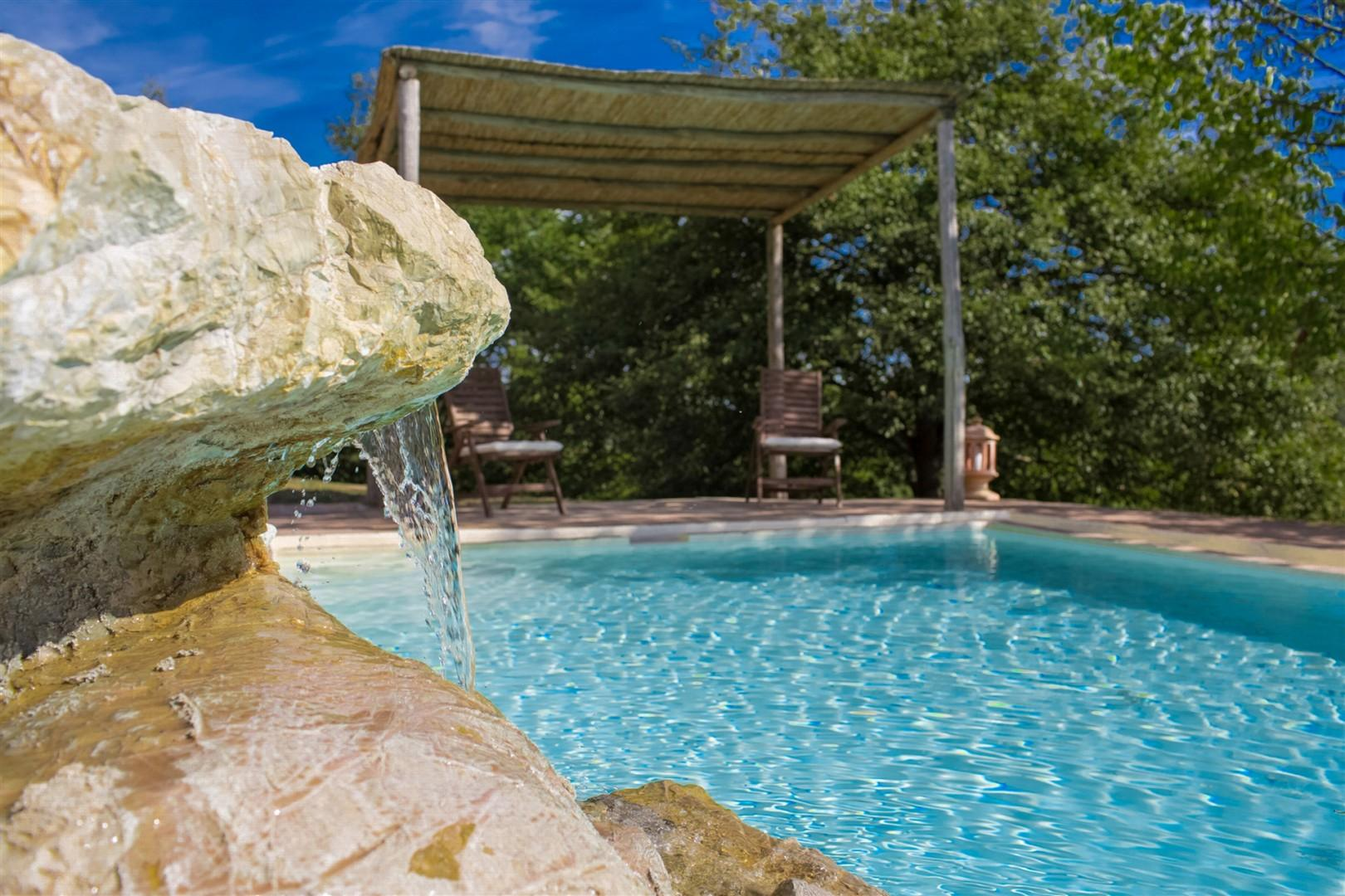The pool has a pleasant waterfall element. A pergola at the far end of the pool provides shade.