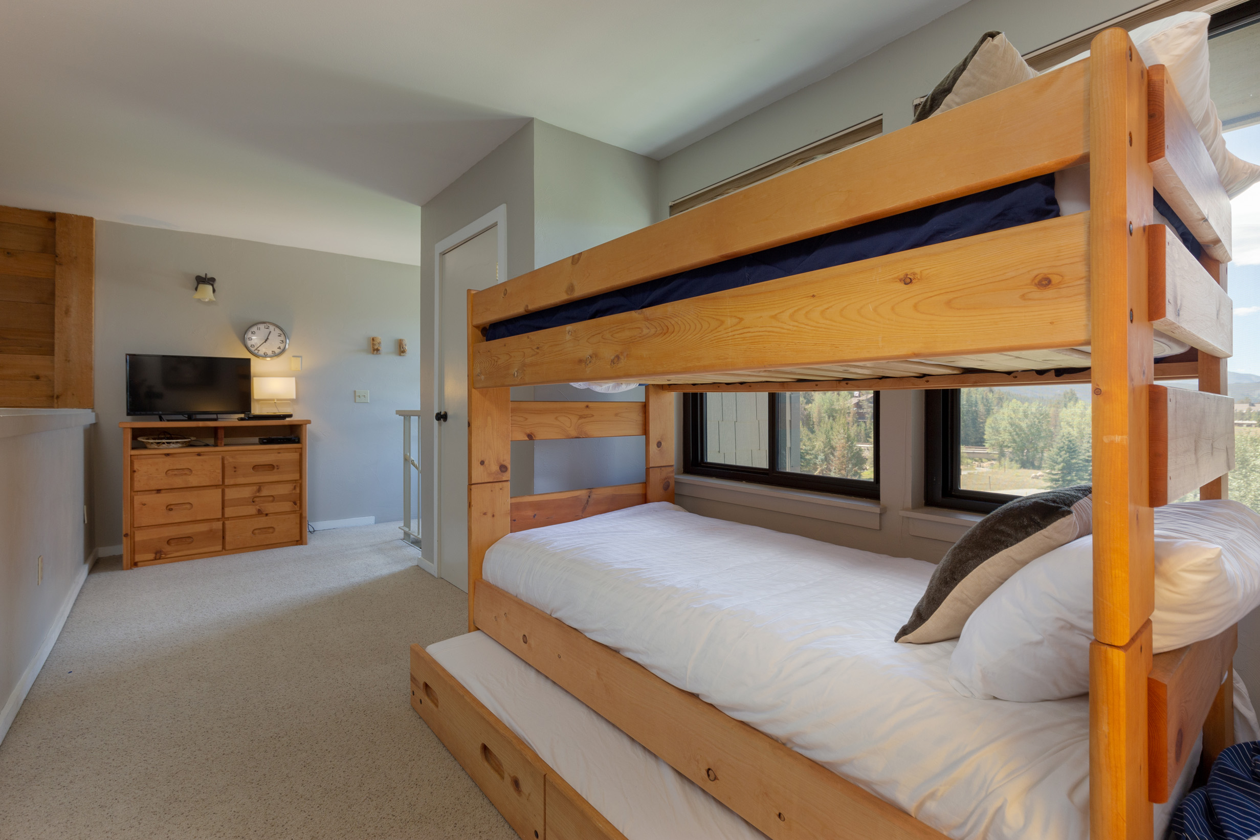 The second bedroom is in the upstairs loft and features a bunk bed with Ivory White Bedding and a twin trundle and a flat screen TV.