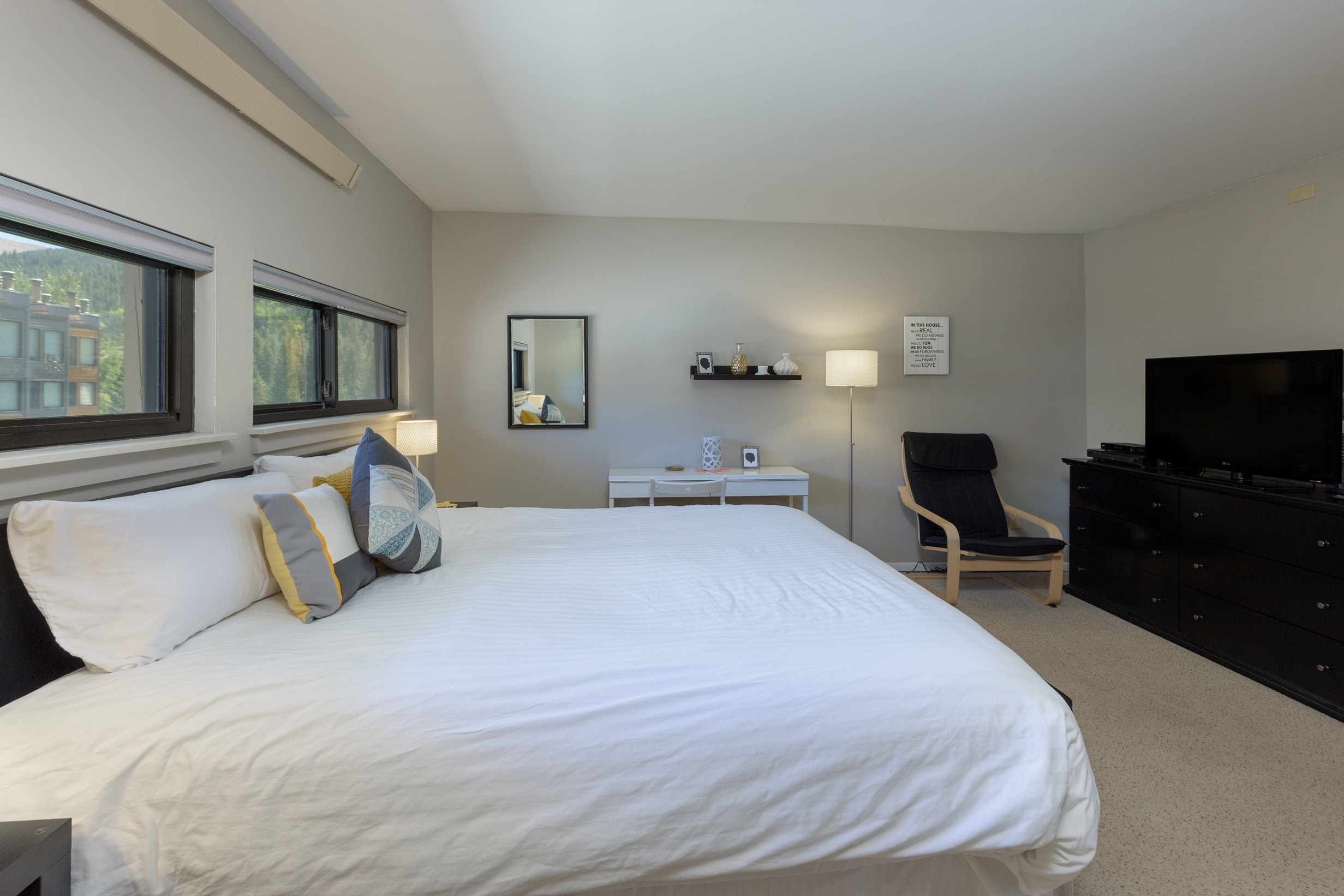 The first bedroom features a king-sized bed with Ivory White Bedding and a flat screen TV.