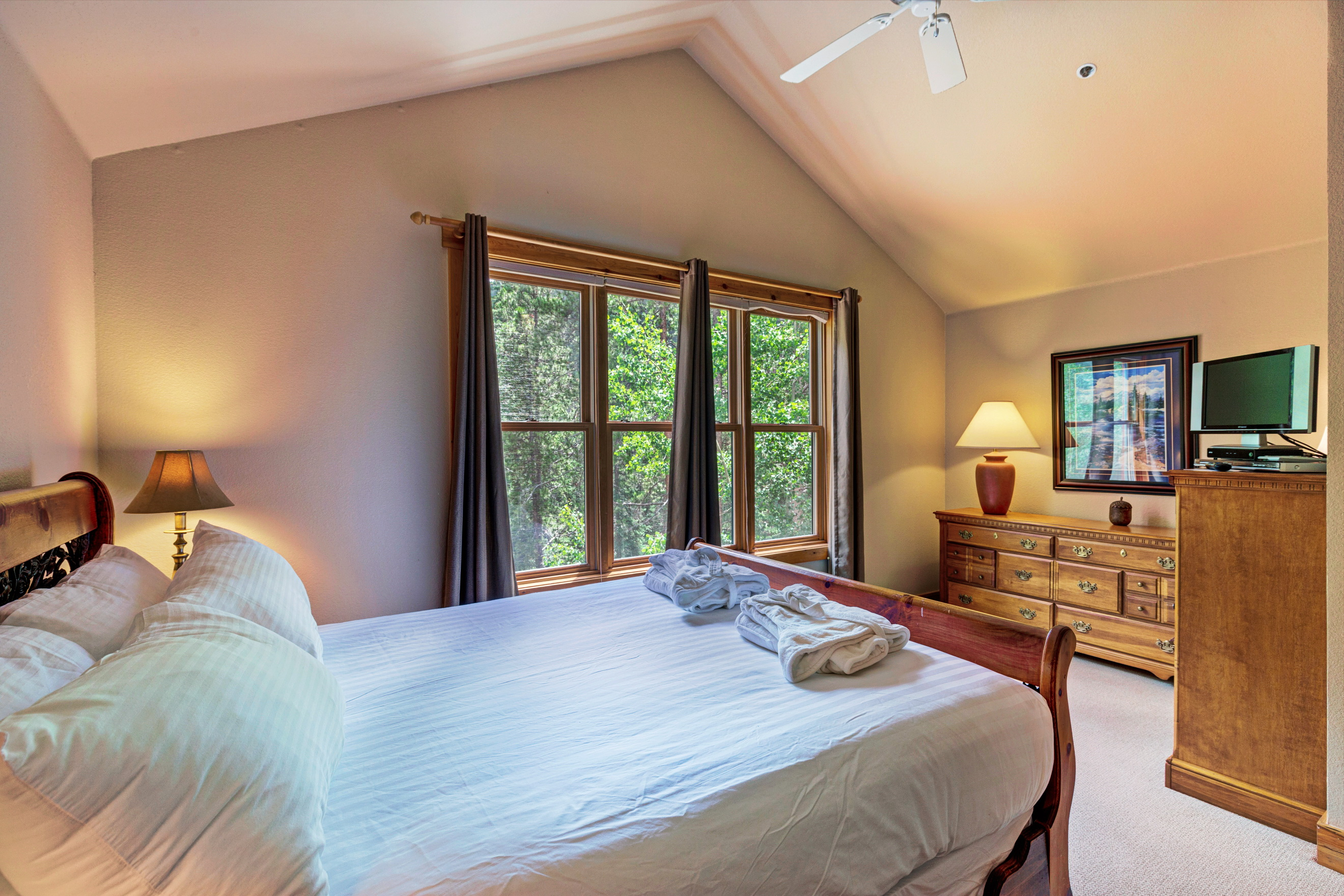 The master bedroom features a queen-sized bed with Ivory White Bedding and a flat screen TV as well as a seating area.