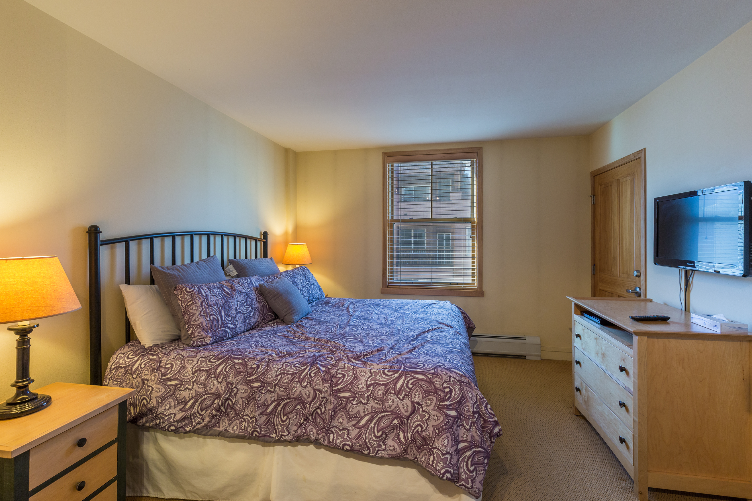The master bedroom features a king-sized bed, mounted flat screen TV and an en suite bathroom.