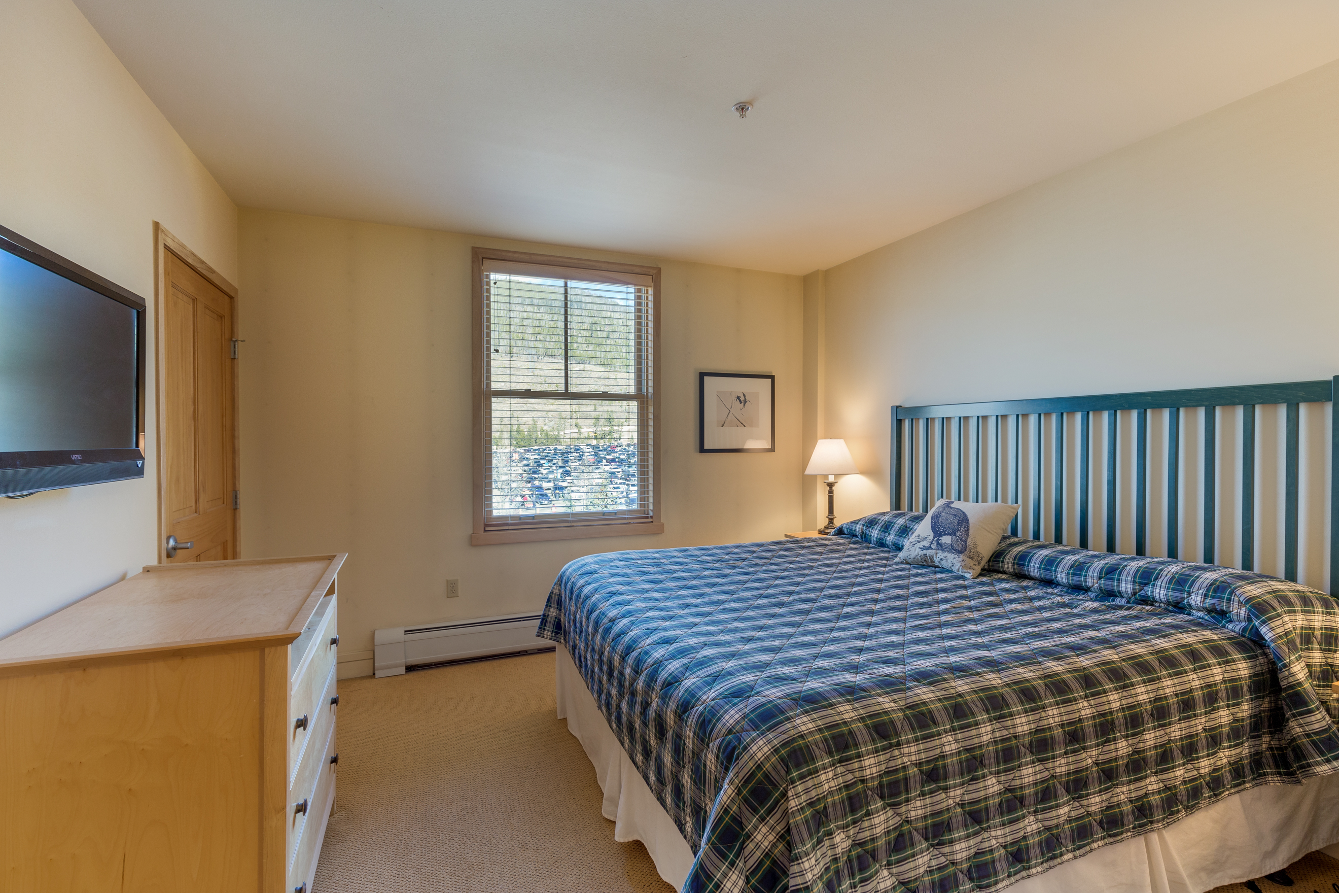 The guest bedroom features a king-sized bed, mounted flat screen TV and its own entrance to the guest bathroom.