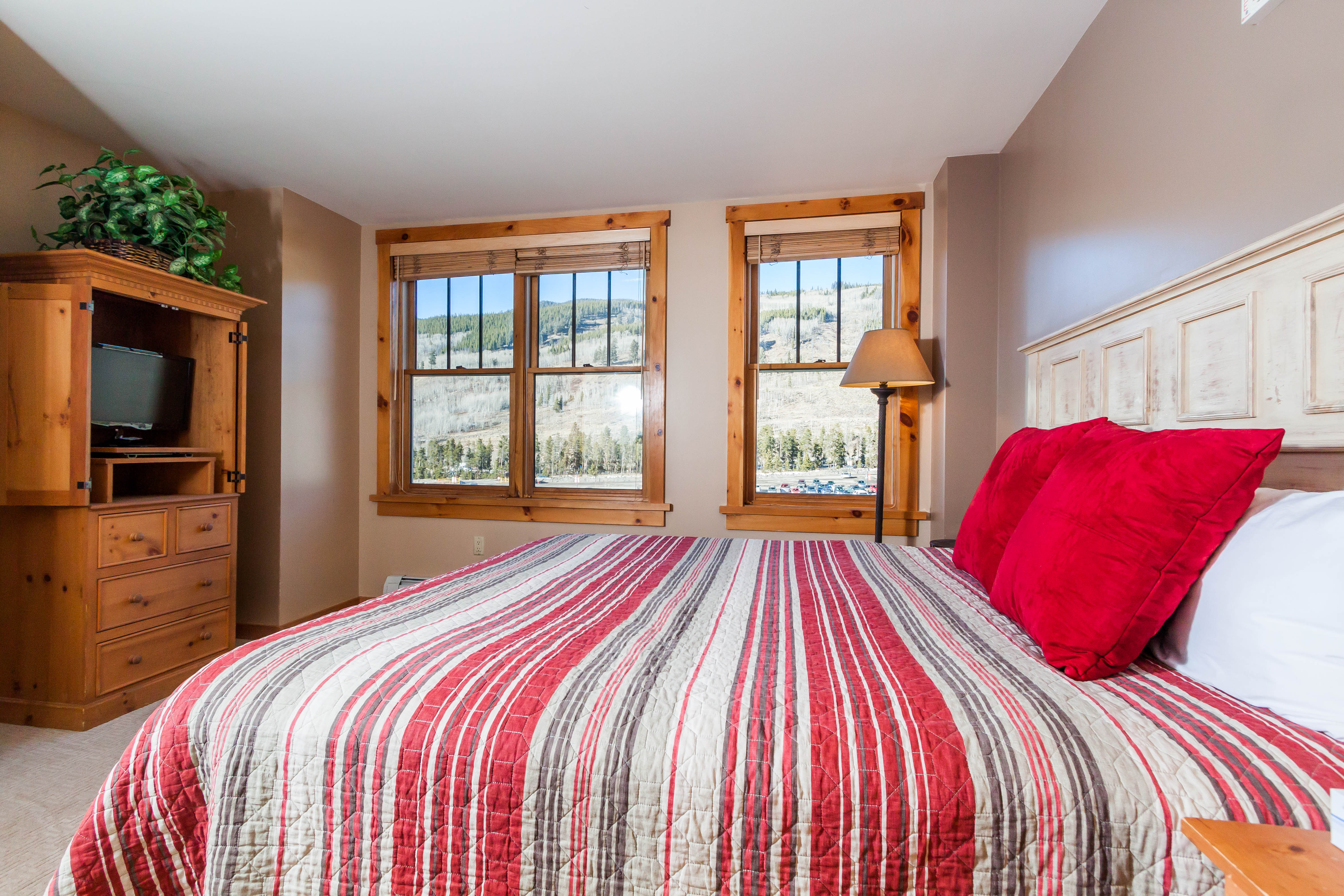 The bedroom features a king-sized bed, a flat screen TV and mountain views.
