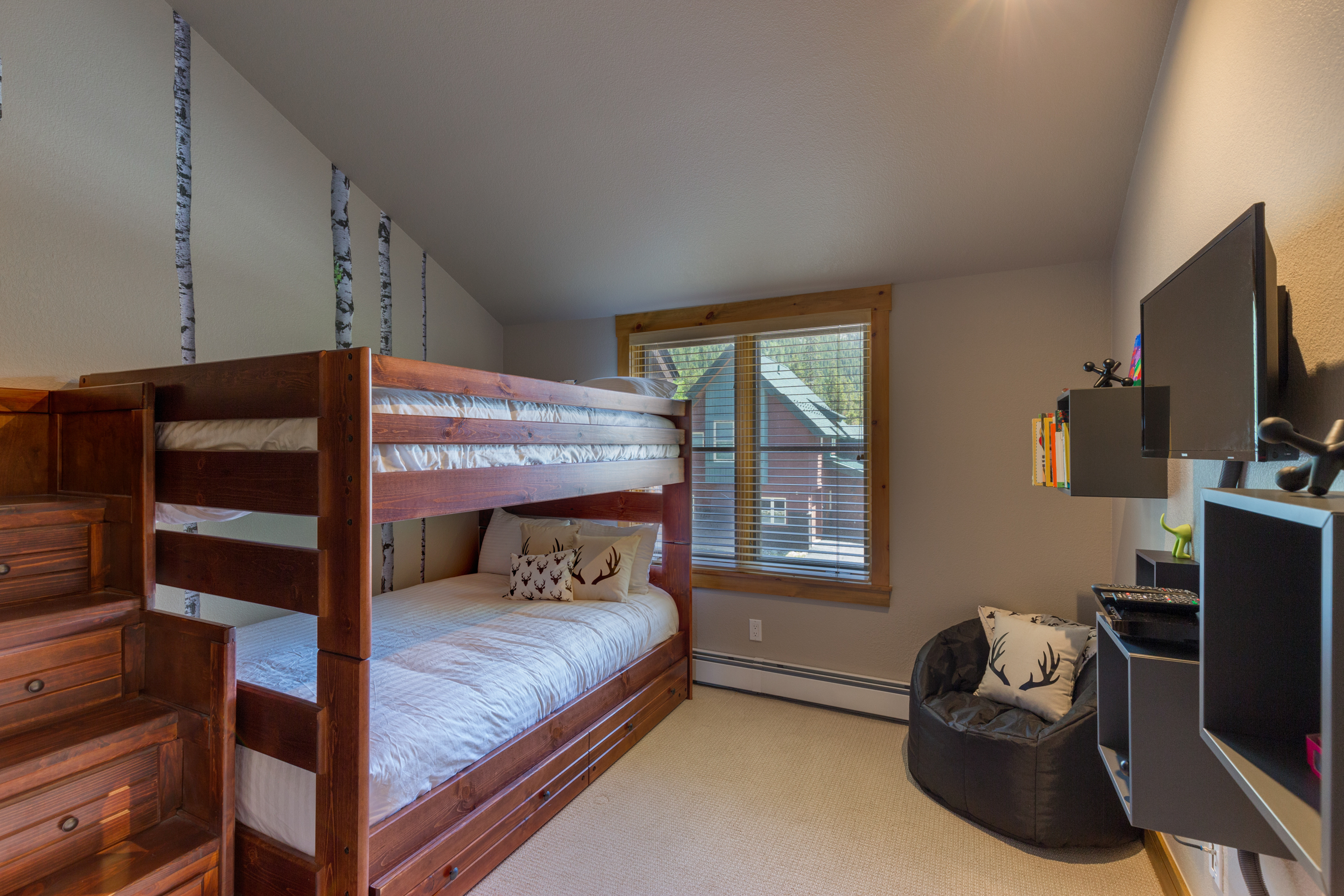 The first guest bedroom features a full-sized bunk bed with Ivory Bedding and a twin trundle that pulls out. There is a mounted flat screen TV and a Blu-ray player.