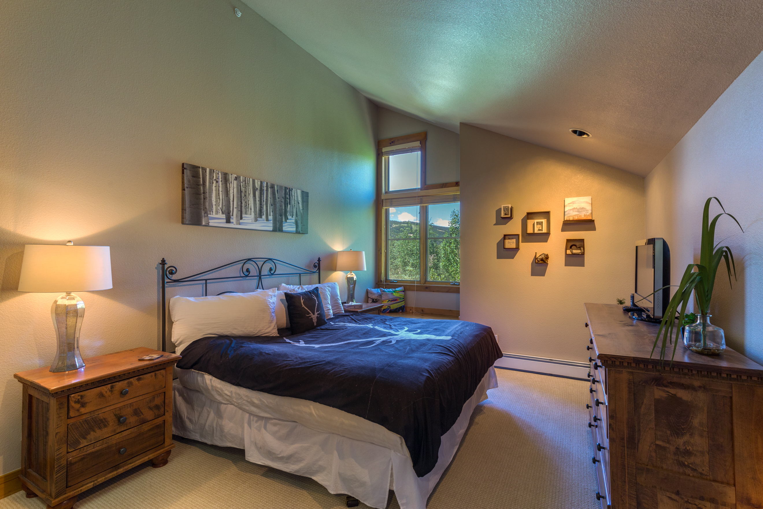 The master bedroom features a king-sized bed with Ivory White Bedding, a flat screen TV and a window seat with beautiful views.