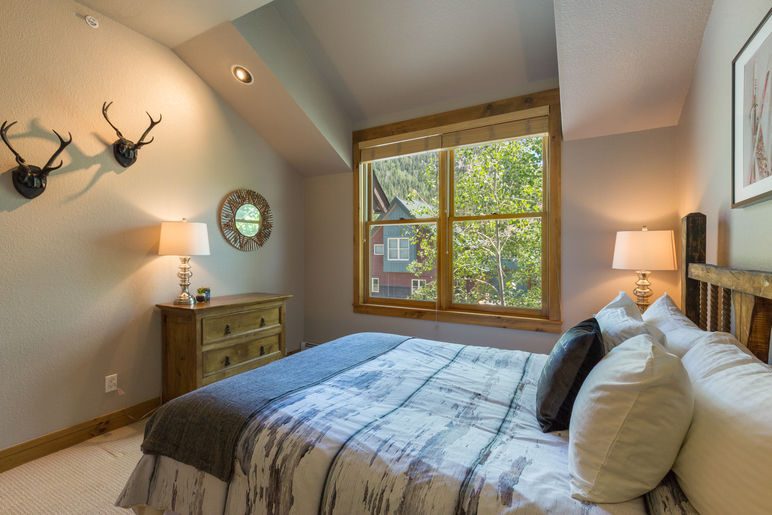 The second guest bedroom features a queen-sized bed with Ivory White Bedding.