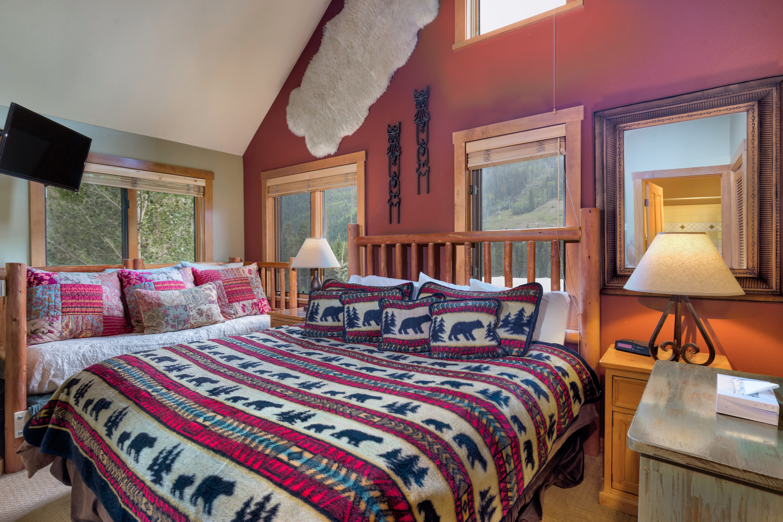 The second master bedroom features a king-sized bed, a twin-sized bed, a flat screen TV and slope views.
