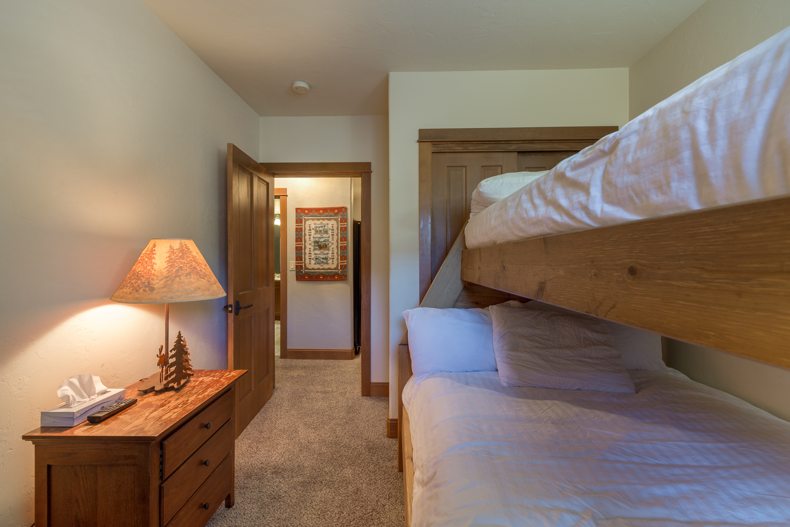 The guest bedroom features a twin-over-full bunk bed with Ivory White Bedding and a flat screen TV.