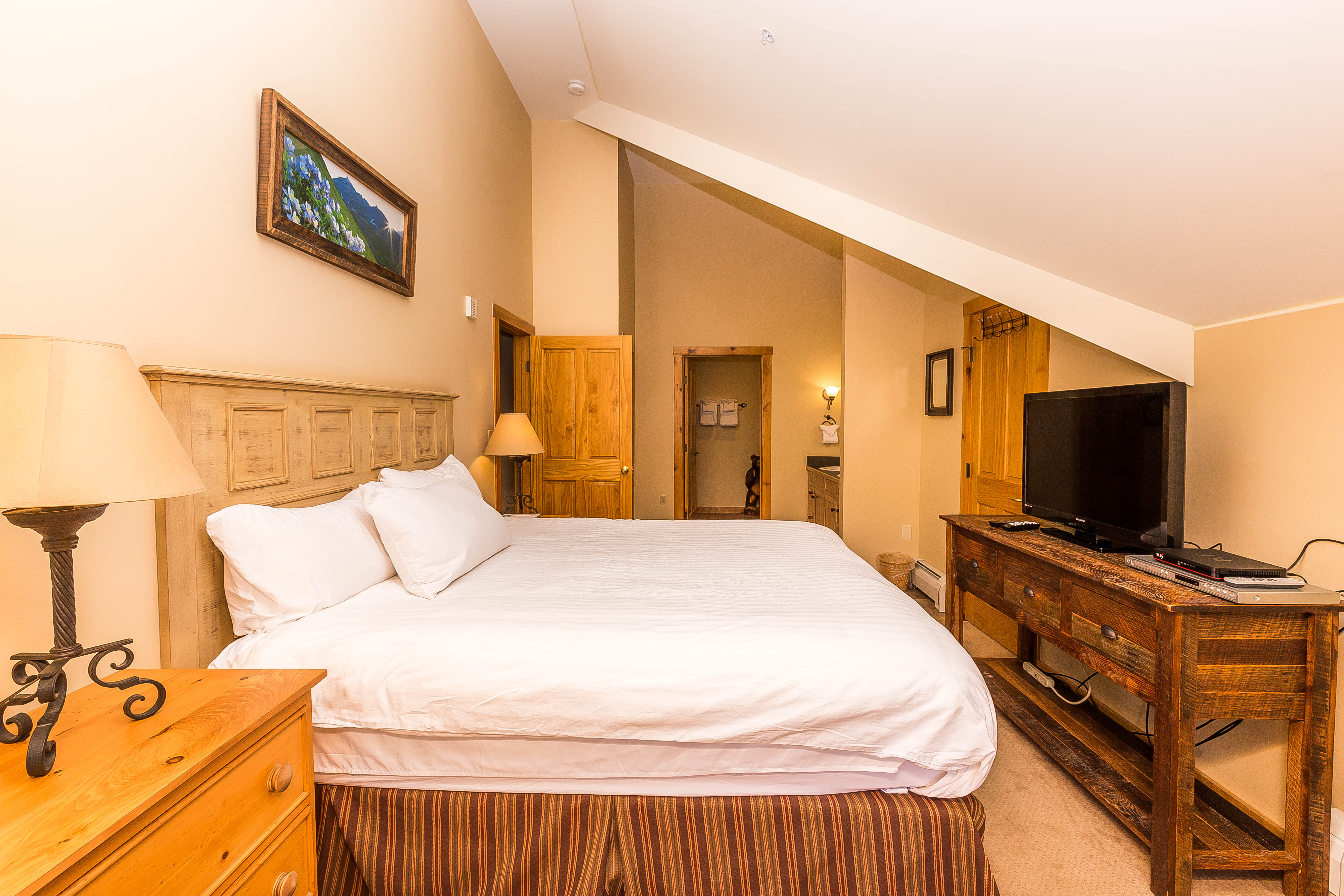 The master bedroom features a king-sized bed with Ivory White Bedding, a flat screen TV and its own access to the private balcony.