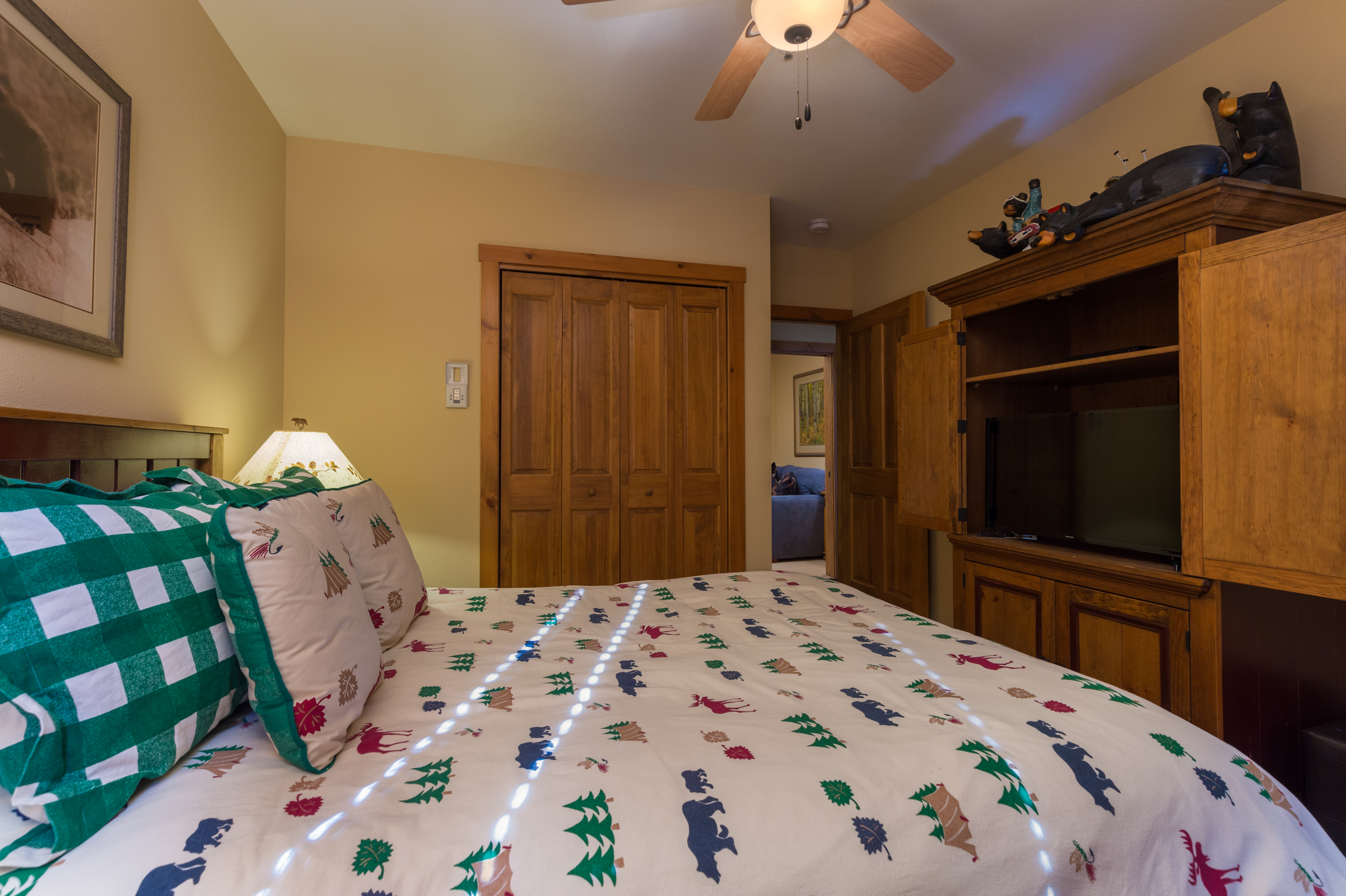 The first guest bedroom features a queen-sized bed and a flat screen TV.