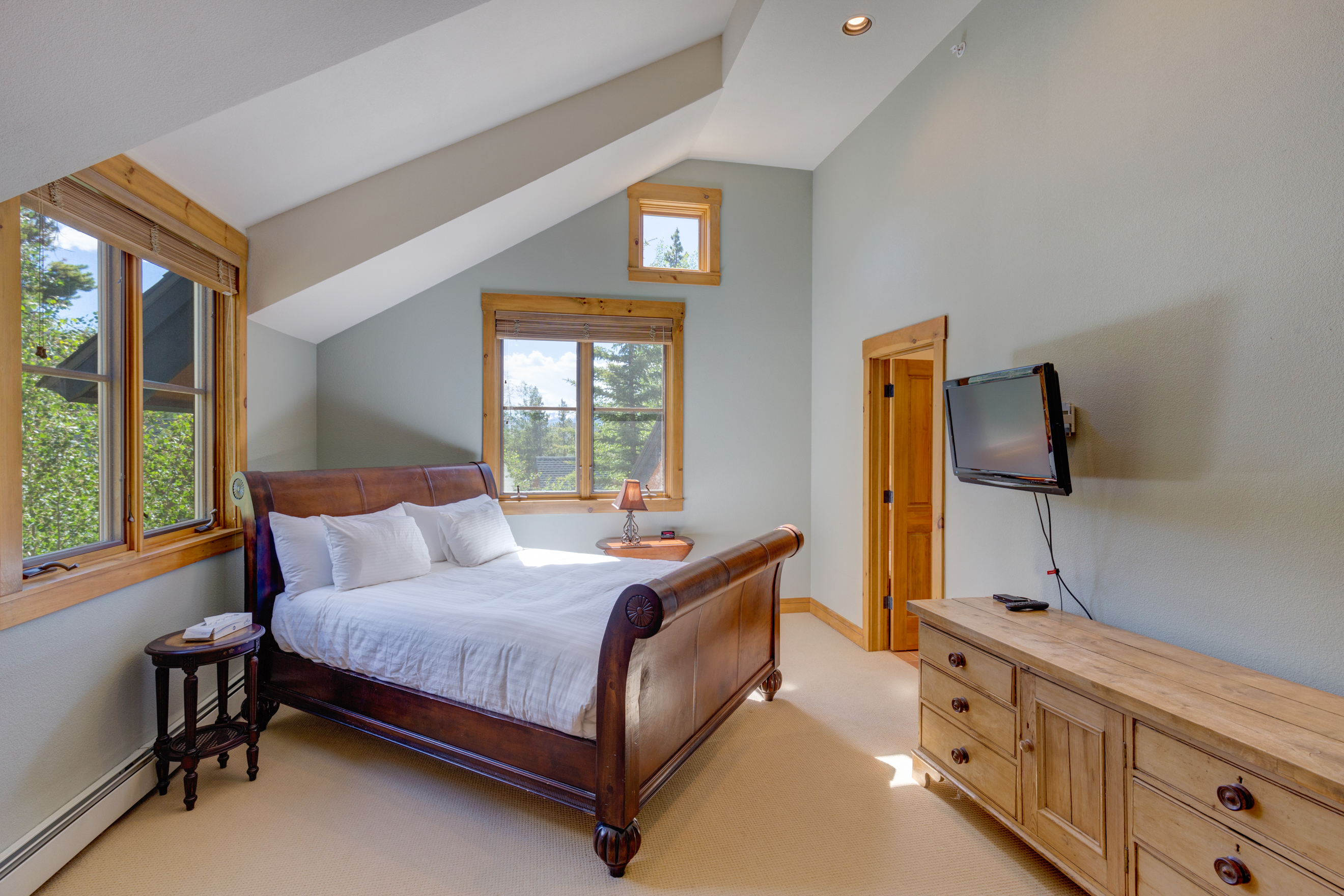 The master bedroom features a queen-sized bed and a mounted flat screen TV.
