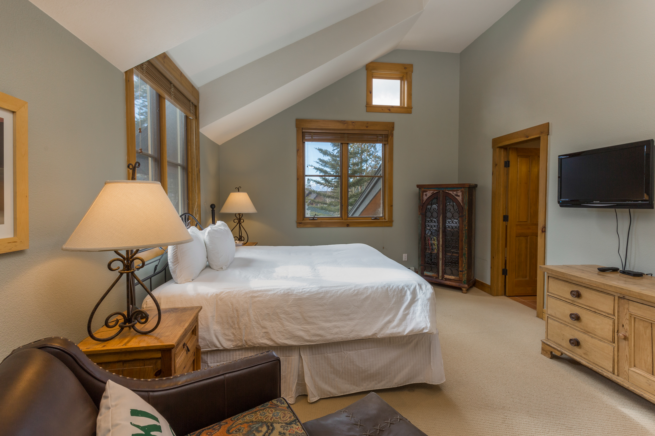 The master bedroom features a queen-sized bed, a mounted flat screen TV and a seating area.
