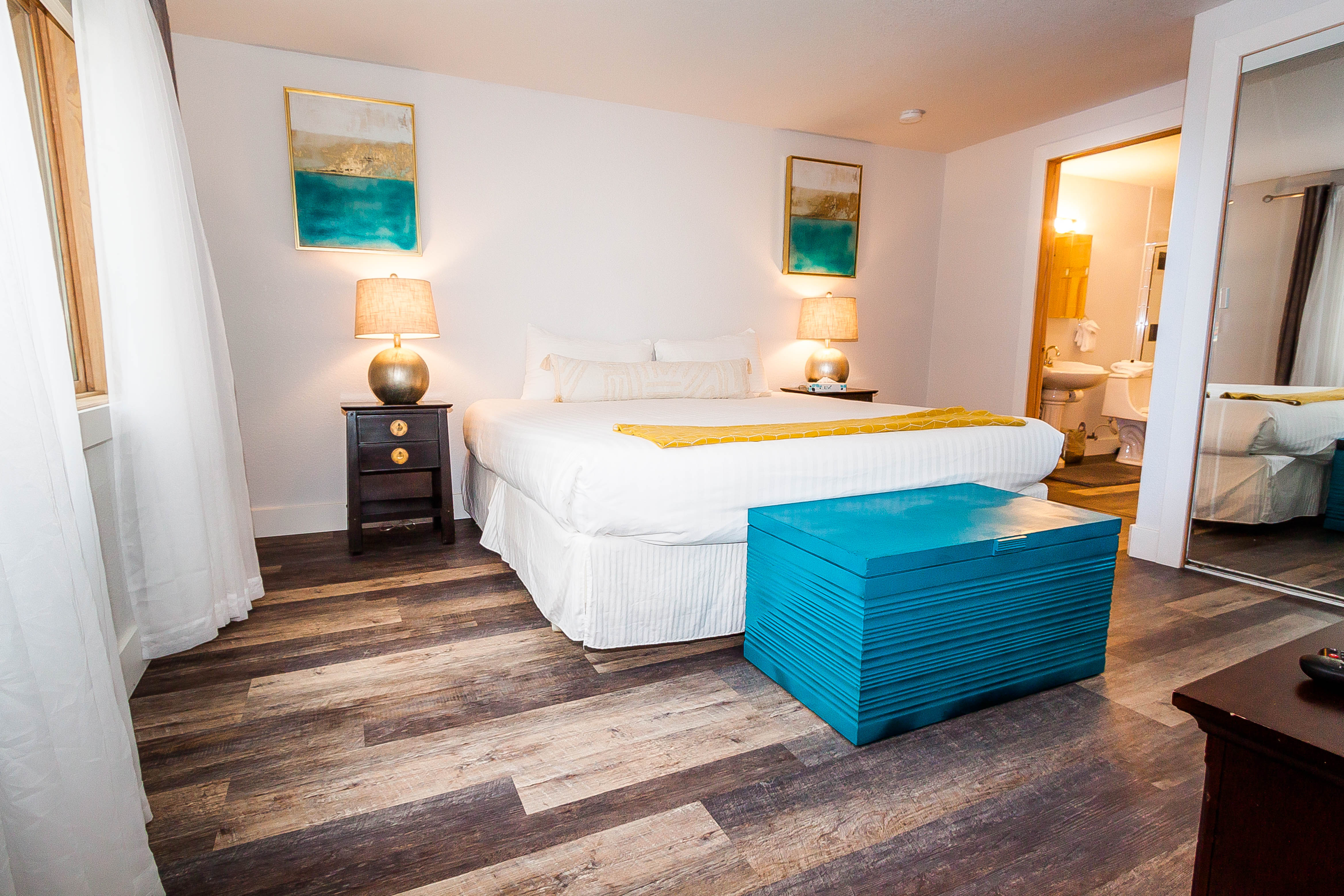 The bedroom features a king-sized bed with Ivory White Bedding and a flat screen TV.