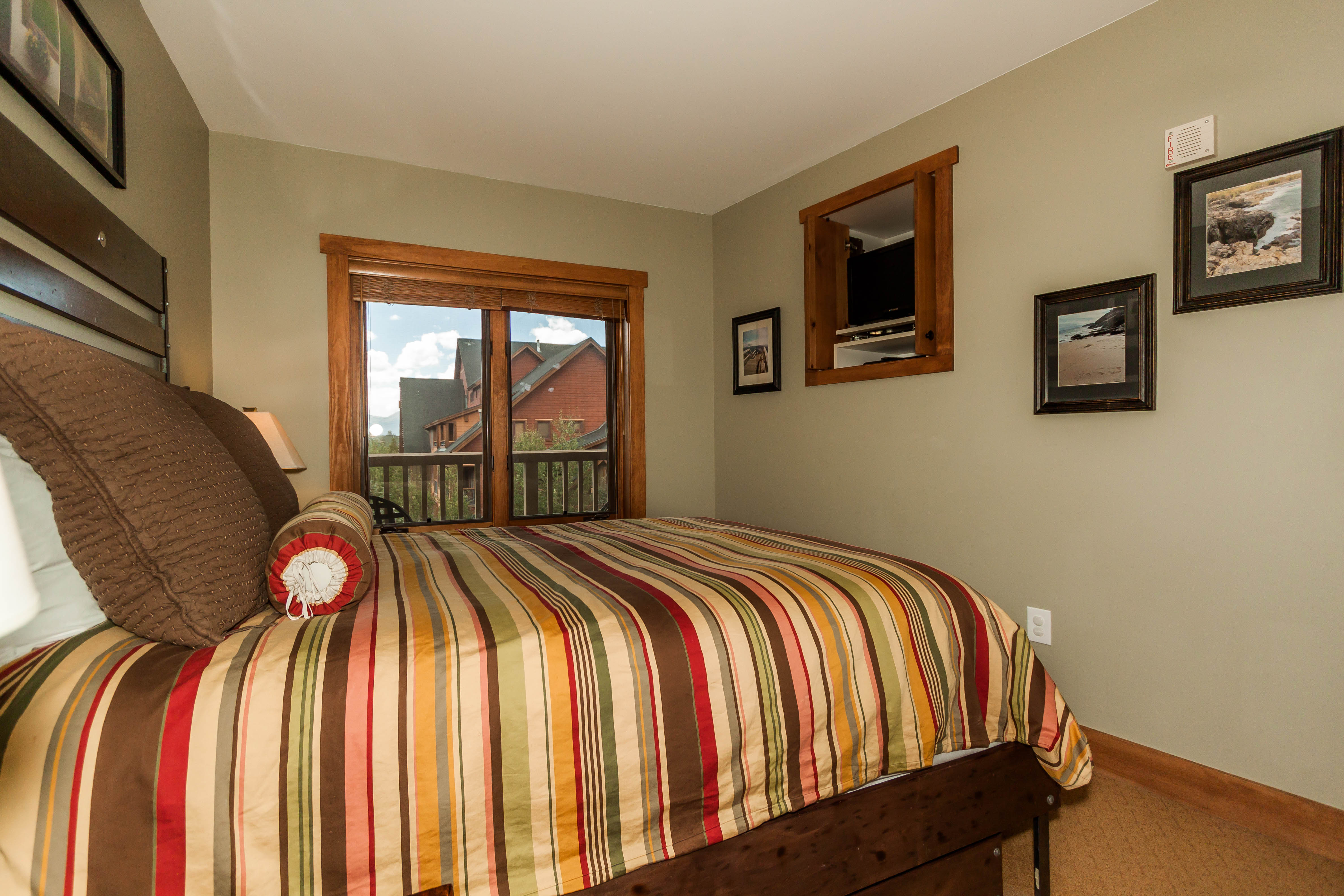 The bedroom features a queen-sized and a flat screen TV.