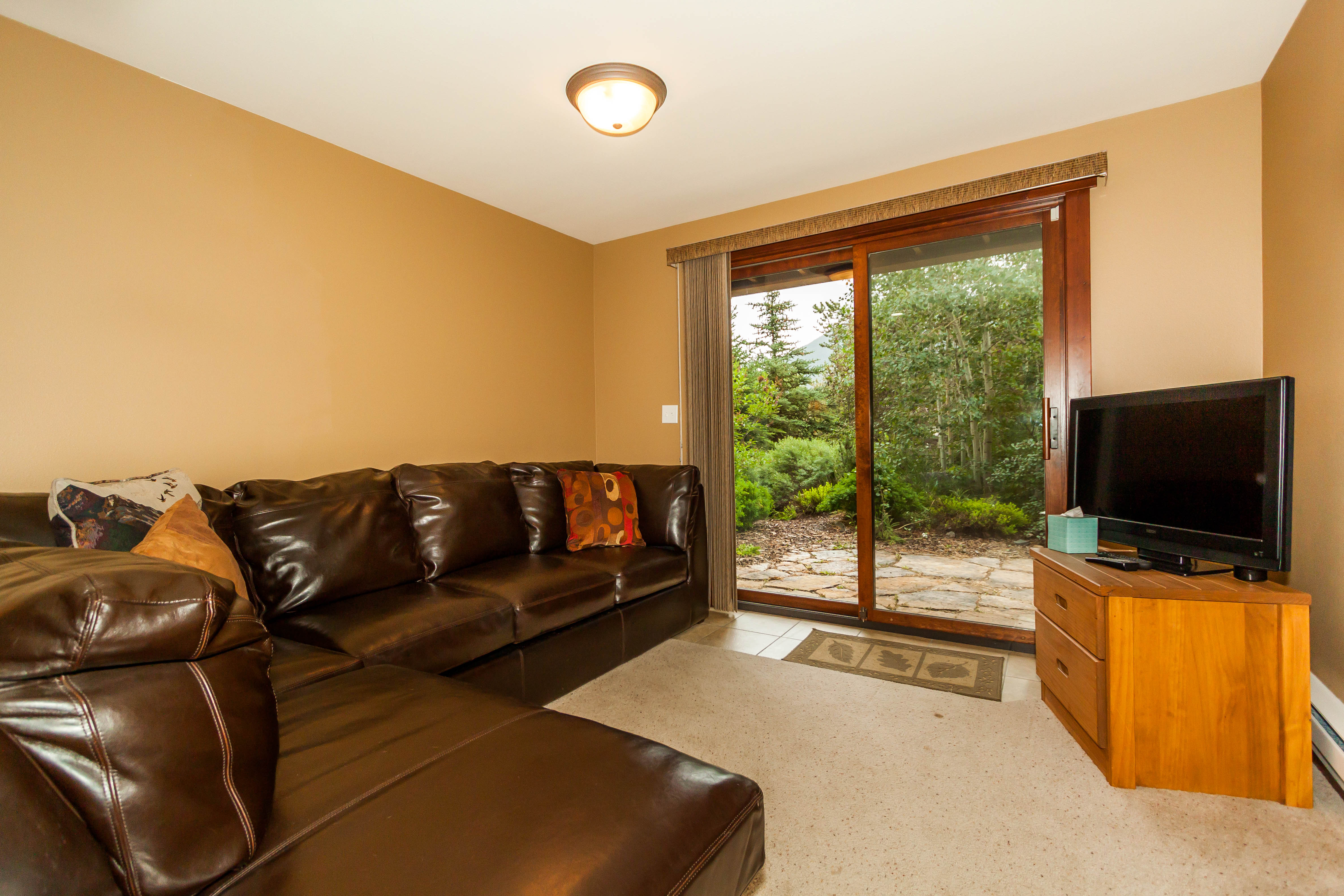 The second guest bedroom can also serve as a den with a sectional, a flat screen TV and a walk-out patio.