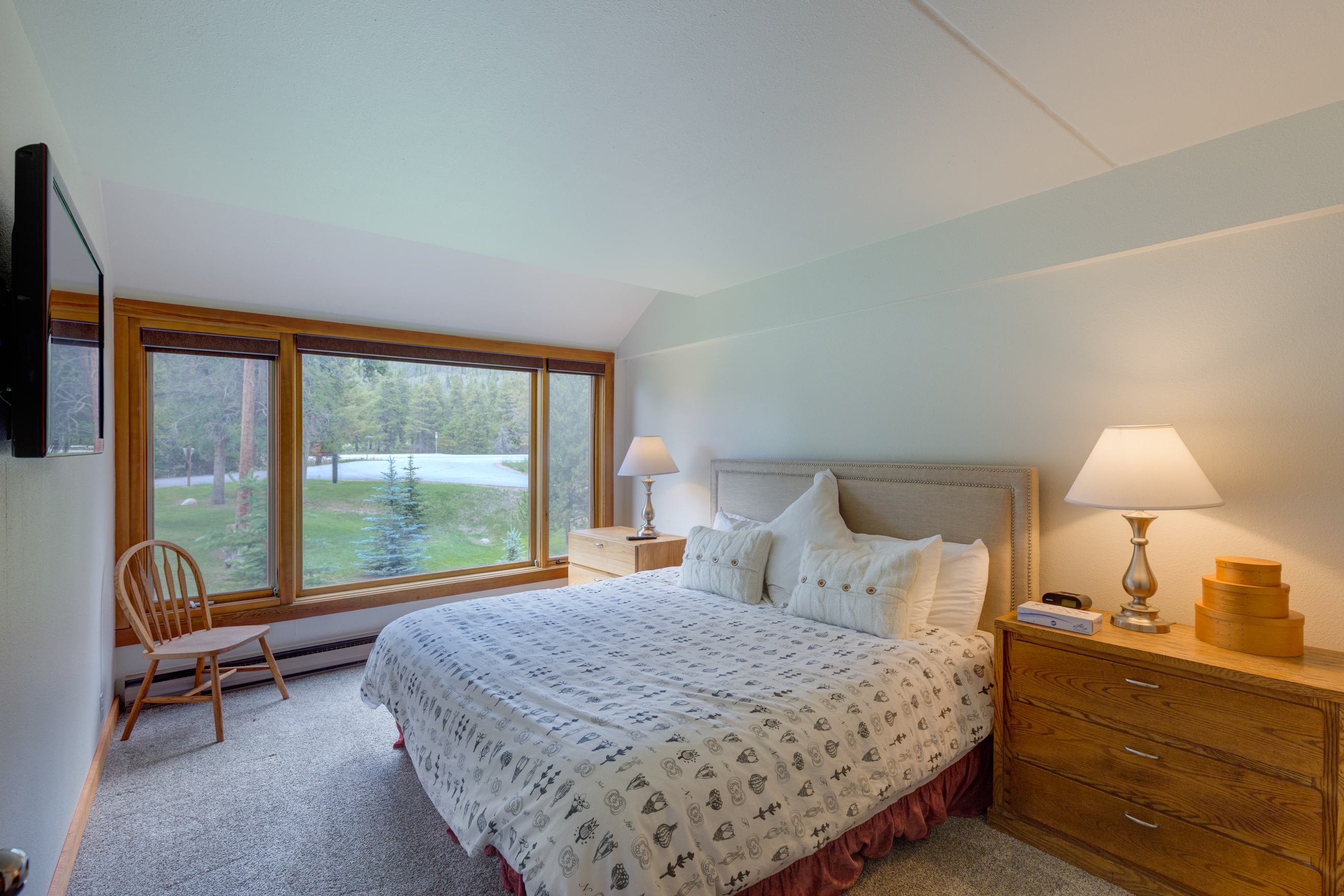 The third guest bedroom features a king-sized bed, large windows and a mounted flat screen TV.