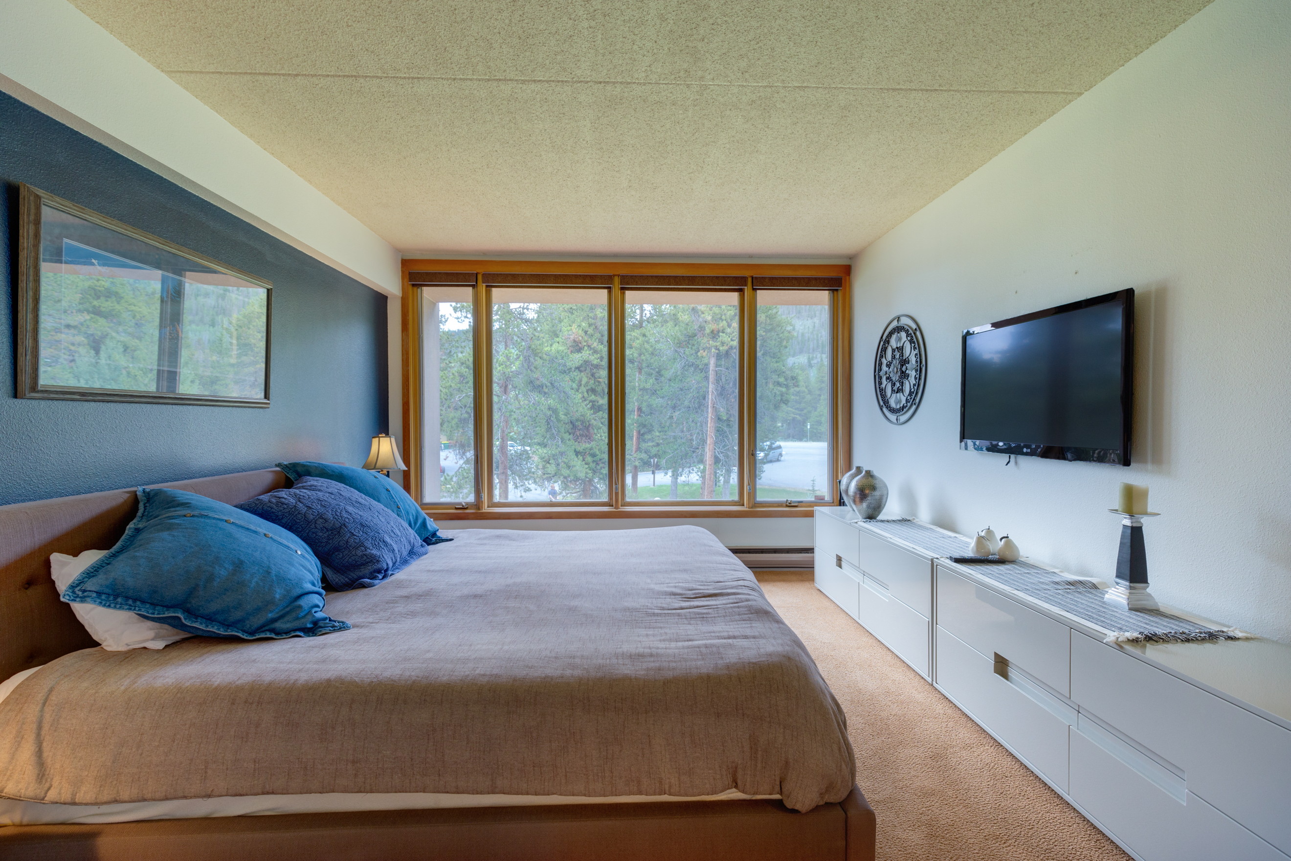 The master bedroom features a king-sized bed, large windows and a mounted flat screen TV.
