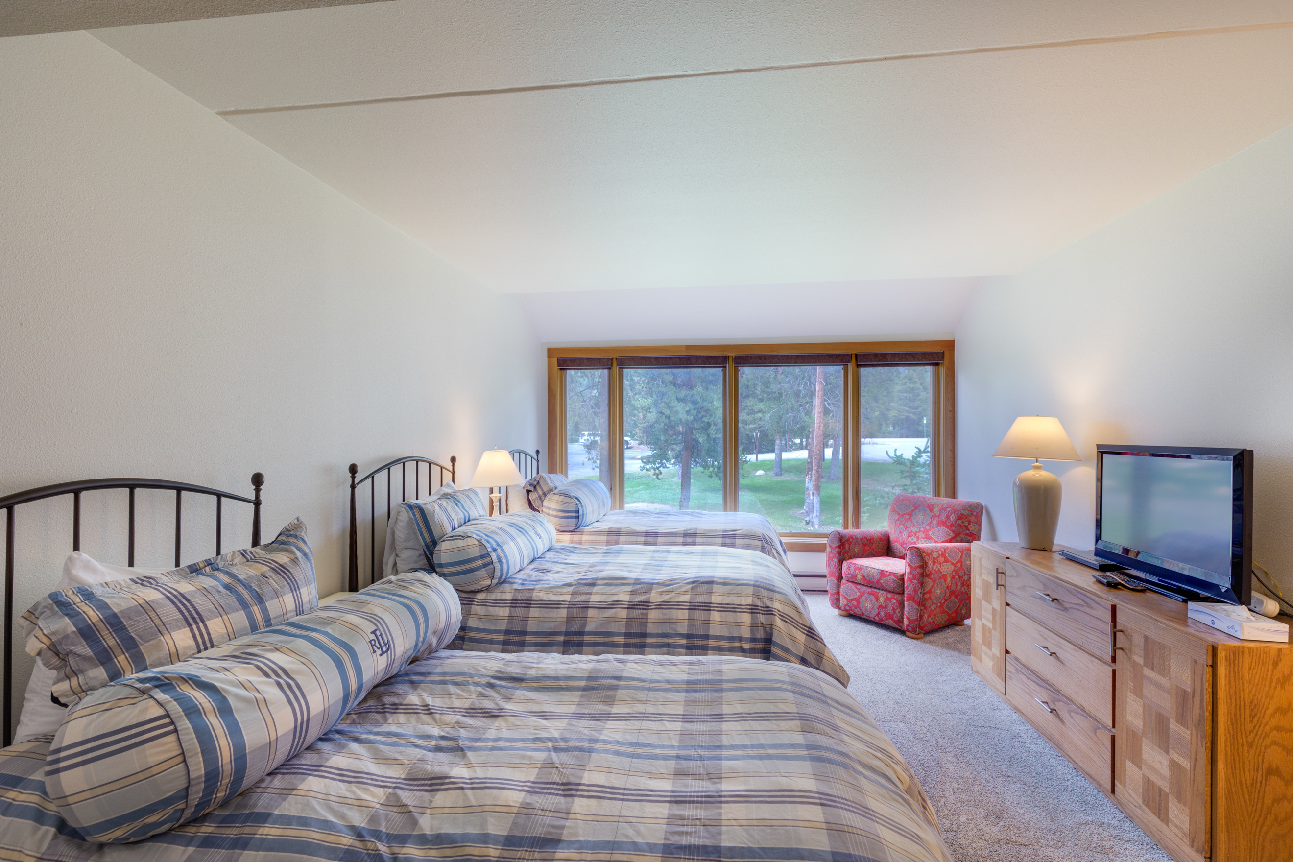 The second guest bedroom features three twin-sized beds and a flat screen TV with DVD player.