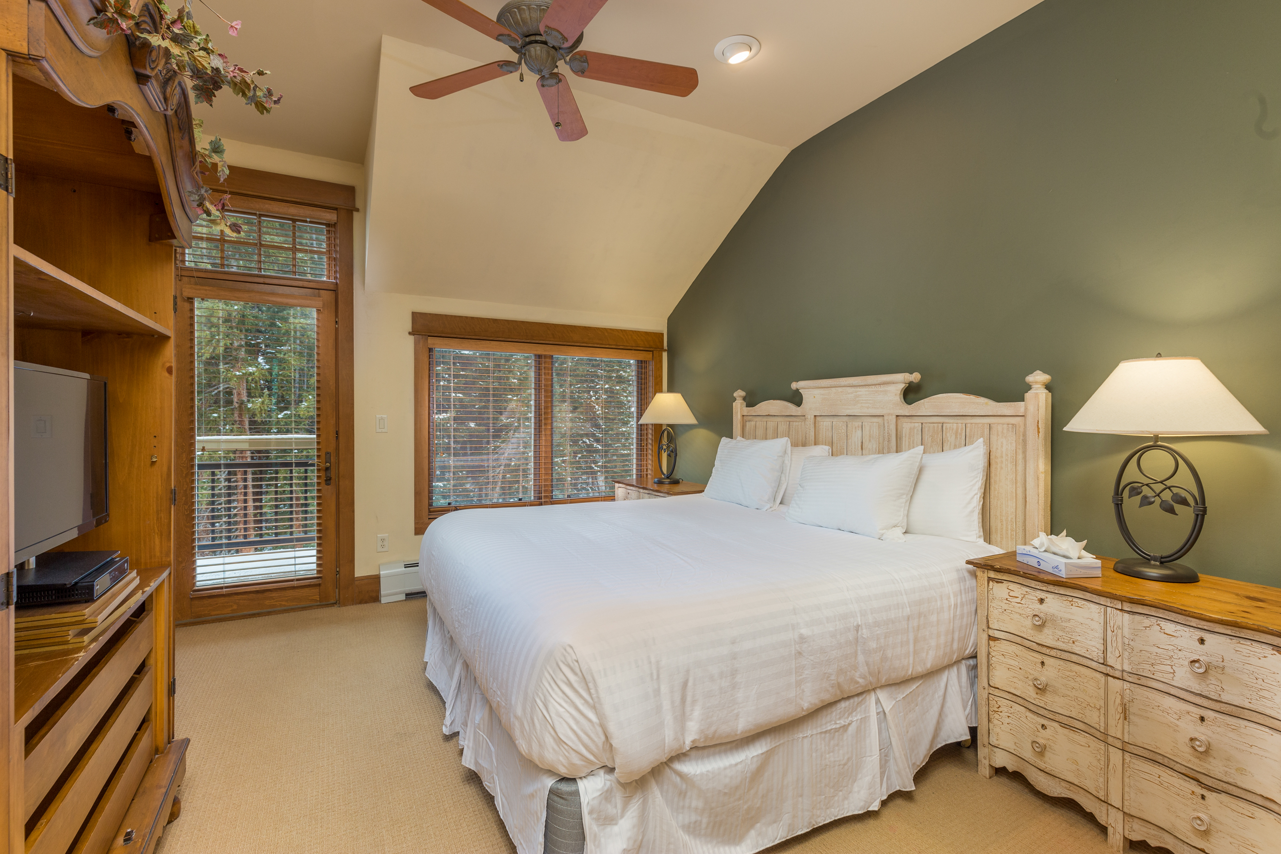 The first master bedroom features a king-sized bed with Ivory White Bedding, a flat screen TV and access to the main balcony.