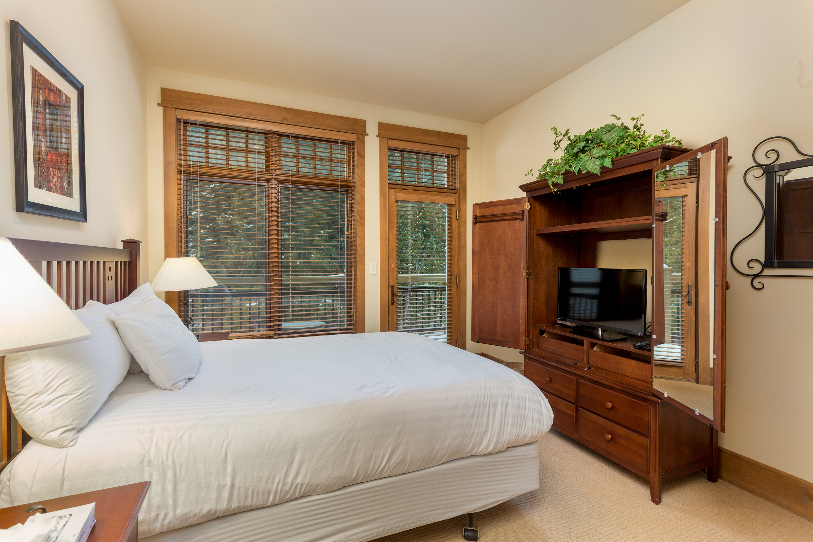 The guest bedroom features a queen-sized bed with Ivory White Bedding, a flat screen TV and access to the main balcony.