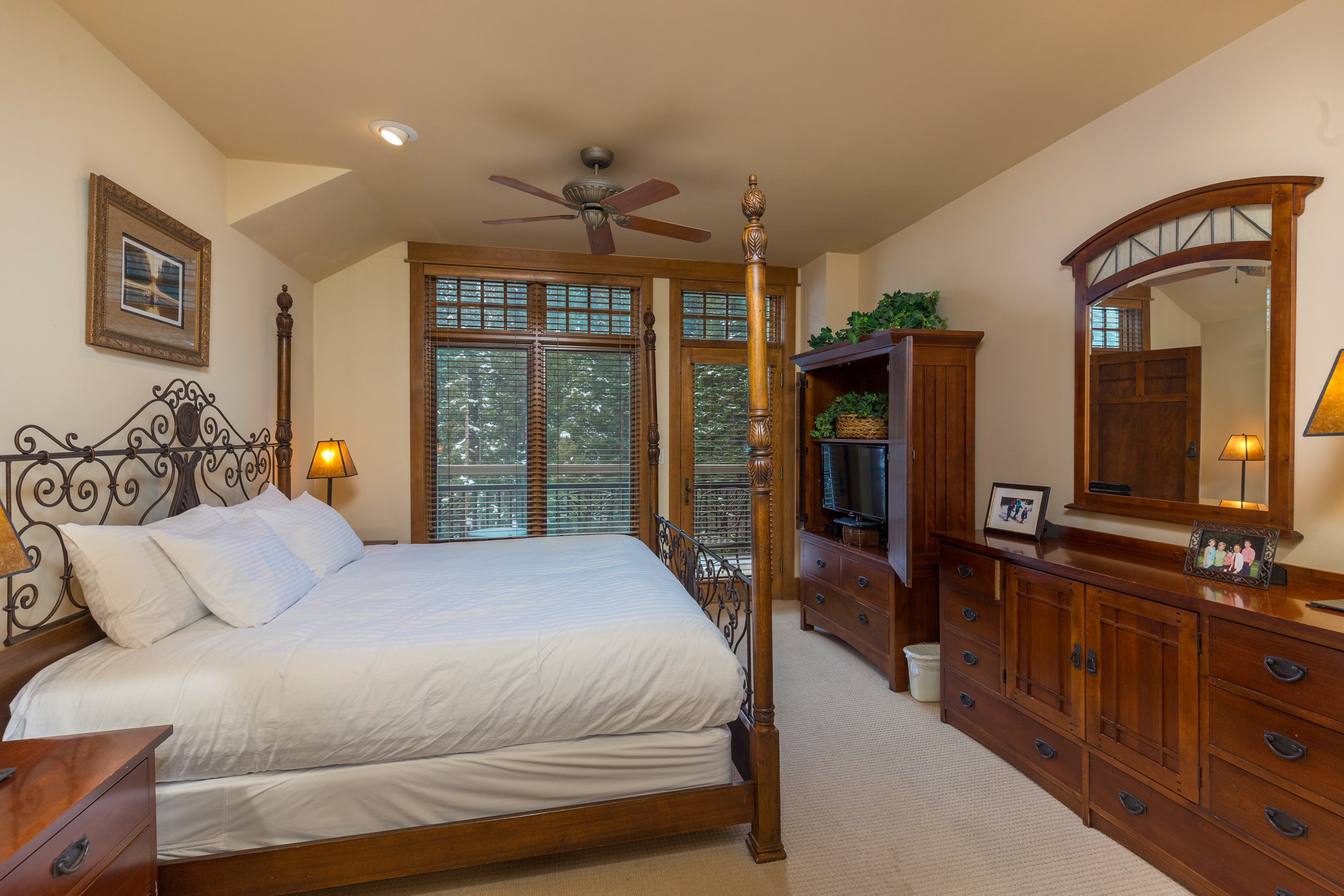 The second master bedroom features a king-sized bed with Ivory White Bedding, a flat screen TV and access to the main balcony.