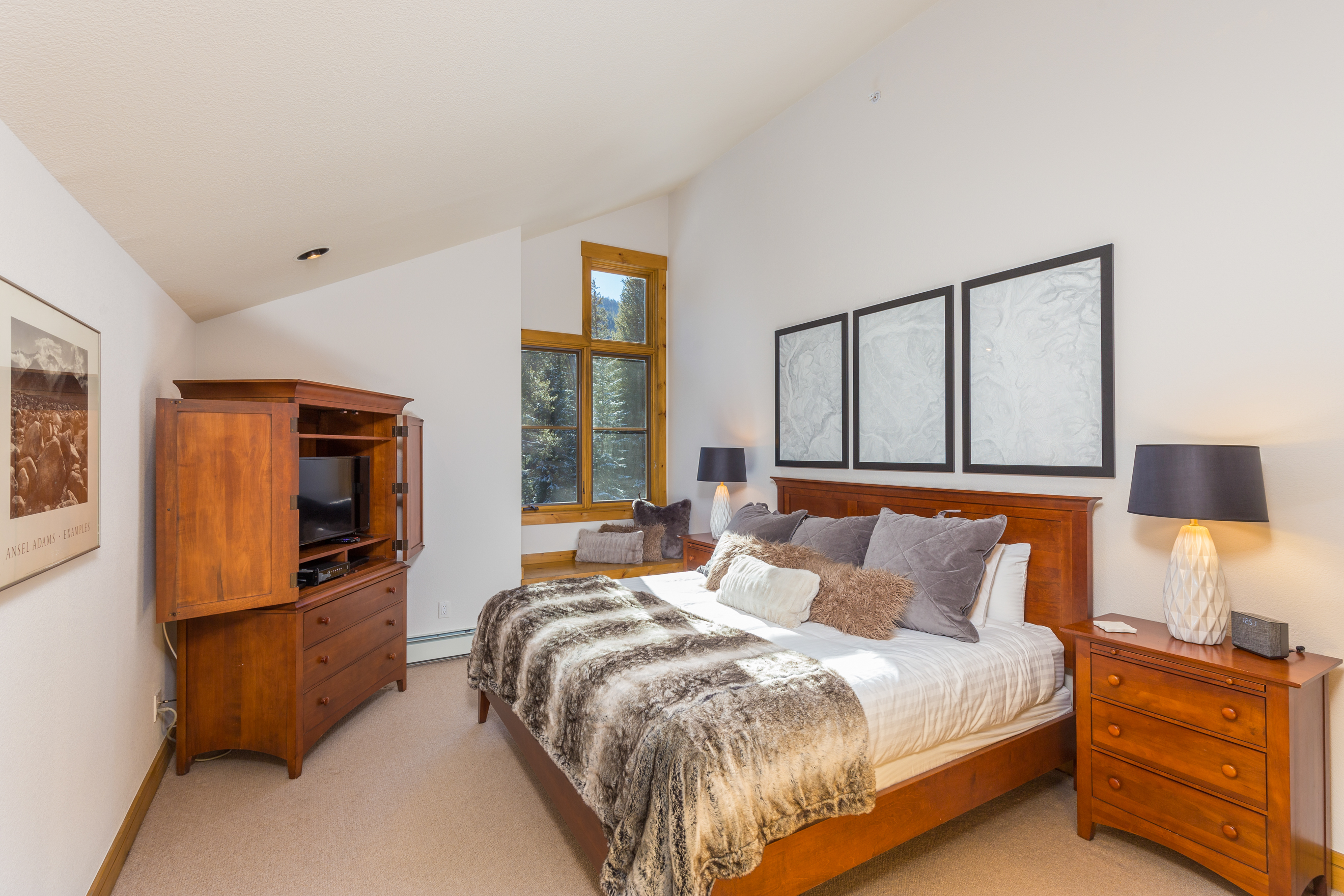 The master bedroom features a king-sized bed with Ivory White Bedding, a flat screen TV and a cozy window seat.