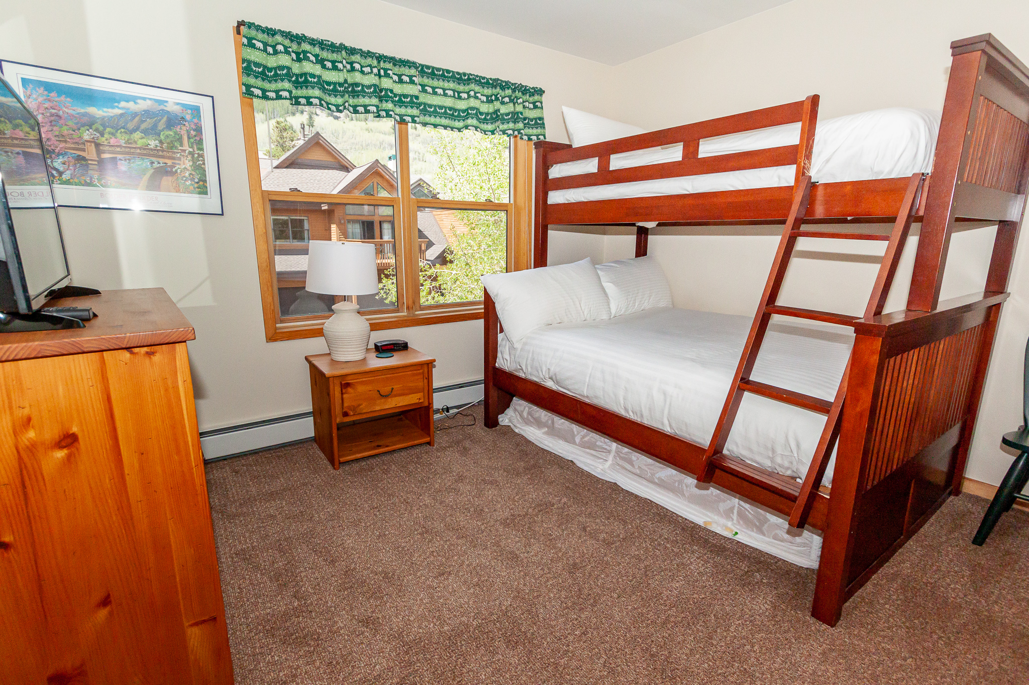 Guest bedroom featuring a twin-over-full bunk bed and flat screen TV.