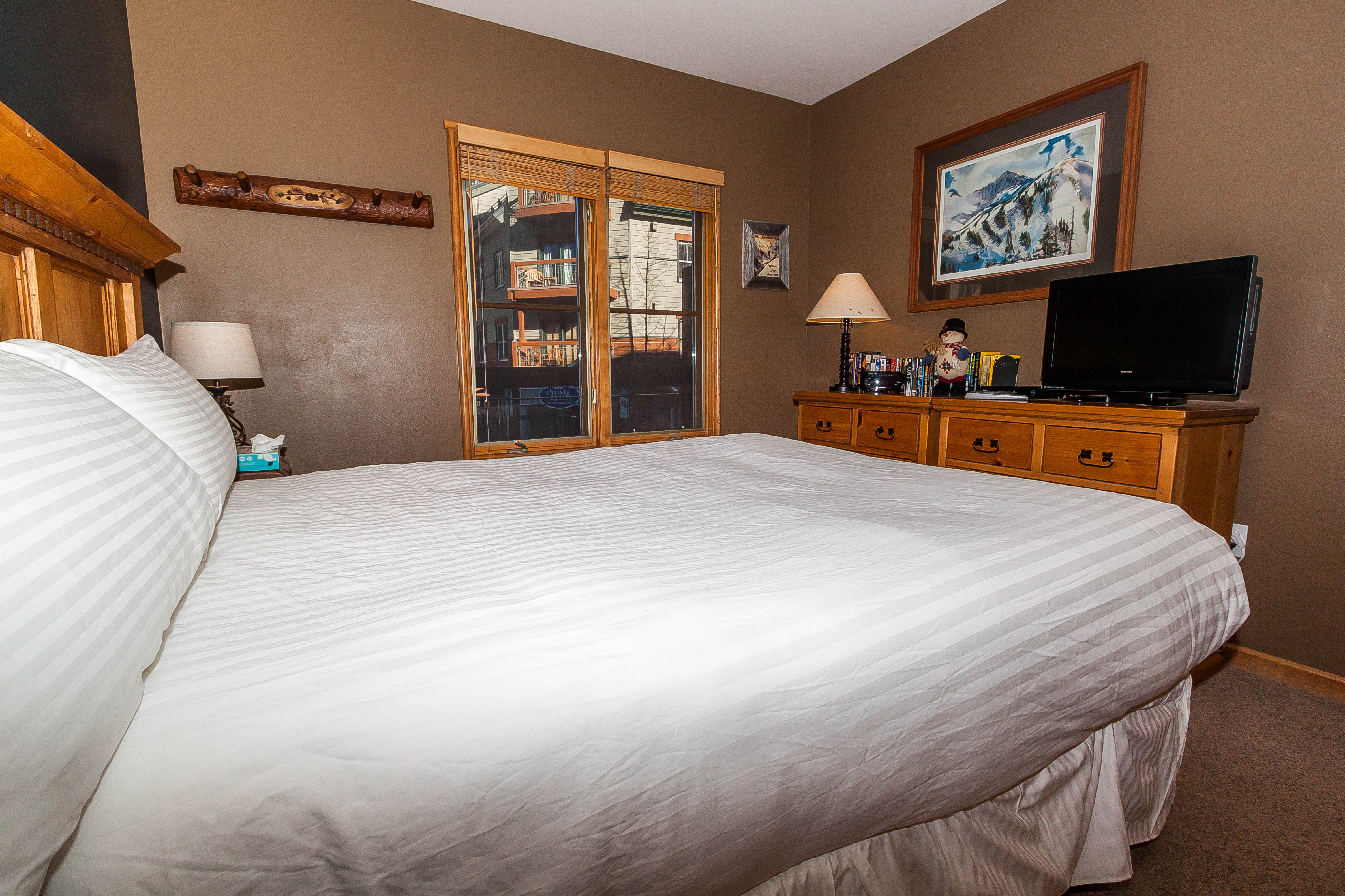 The bedroom features a queen-sized bed with Ivory White Bedding and a flat screen TV with a DVD player.