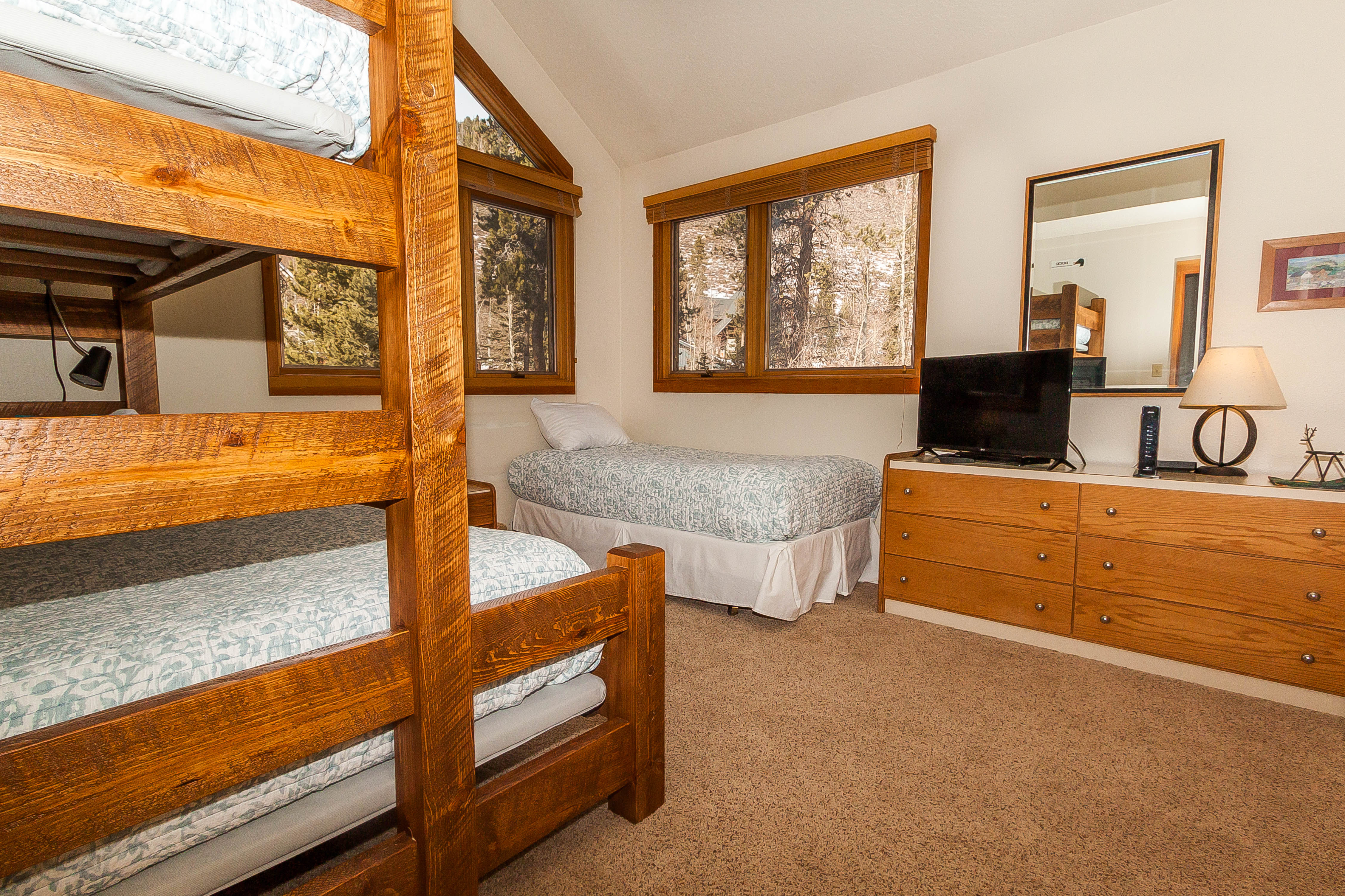 The guest bedroom features a twin-over-queen bunk bed, a twin-sized bed and a flat screen TV.