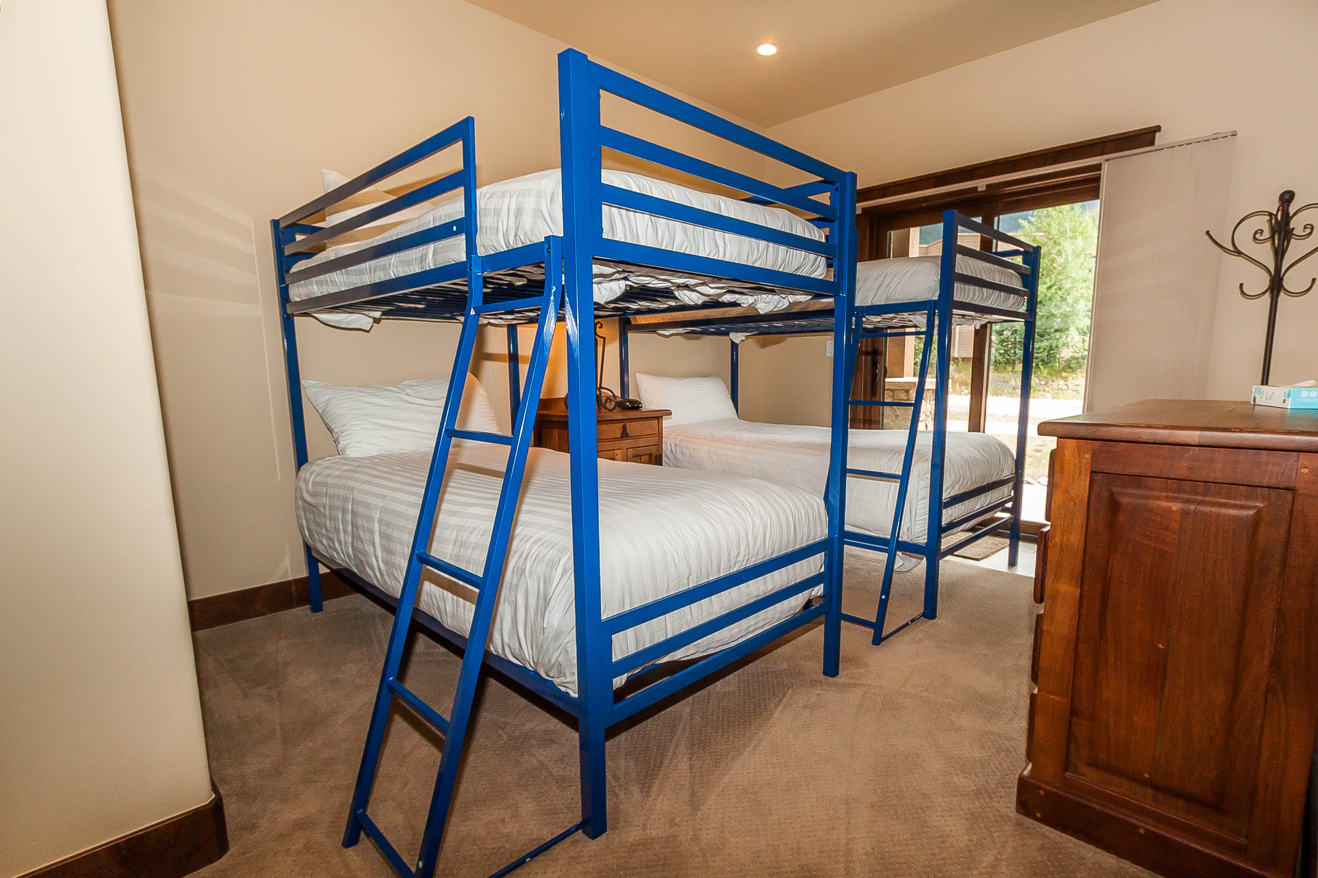 The guest bedroom is downstairs and features two twin-sized bunk beds with Ivory White Bedding and its own private patio.