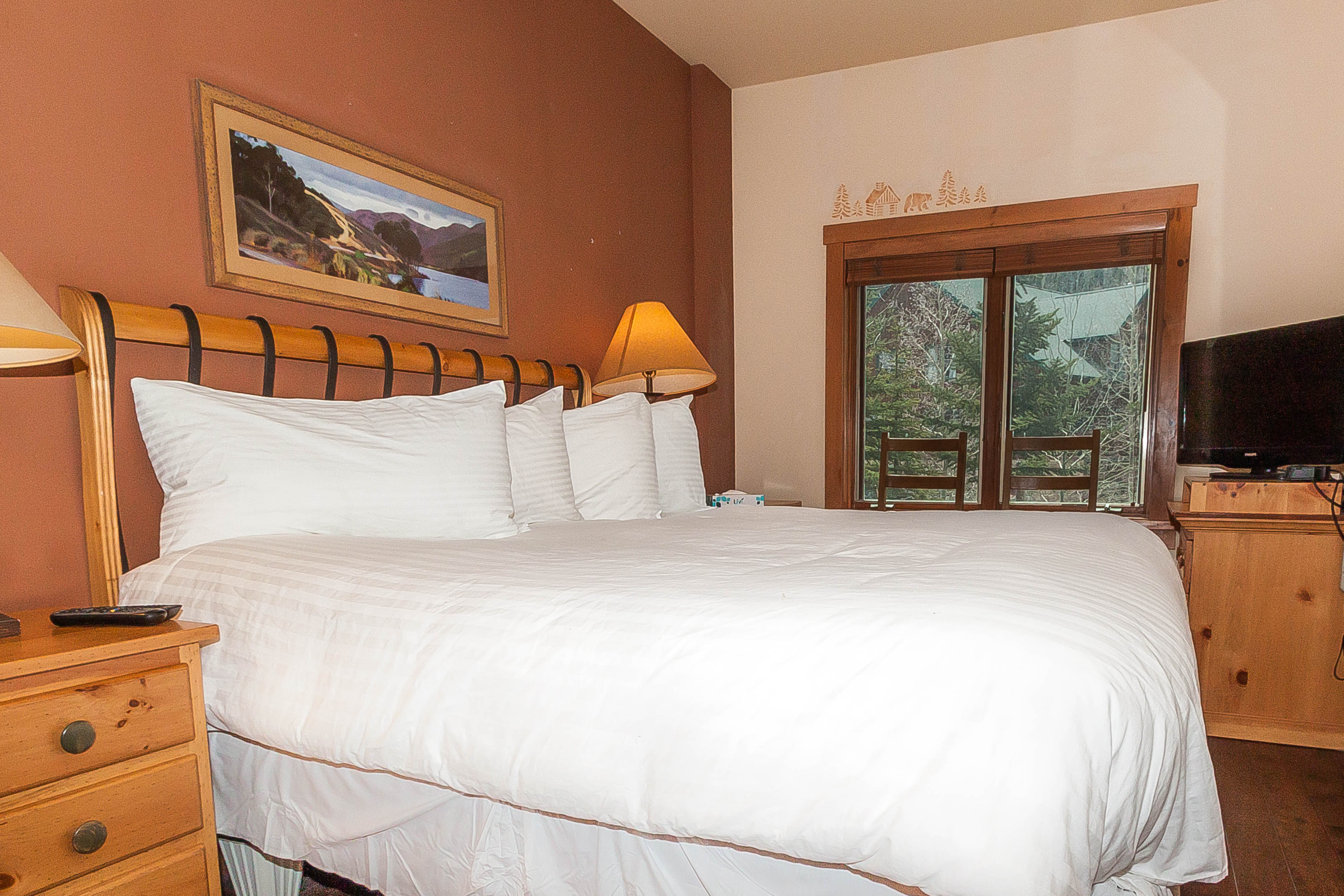 The master bedroom features a king-sized bed with Ivory White Bedding and a flat screen TV.