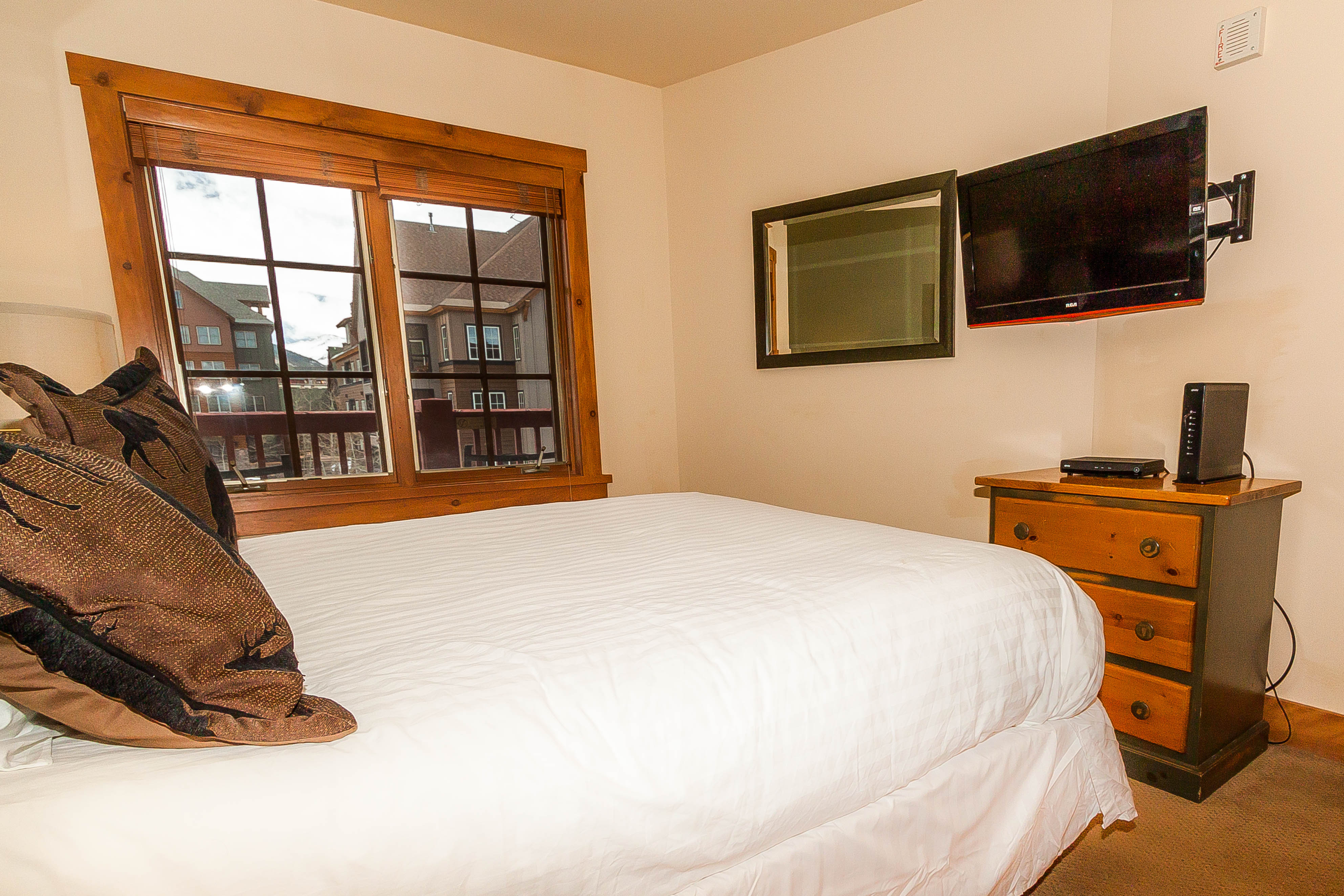 The bedroom features a queen-sized bed with Ivory White Bedding and a mounted flat screen TV.