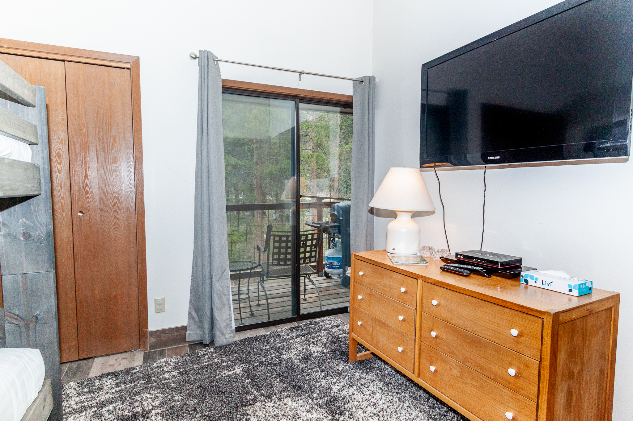 The guest bedroom features a full-over-full bunk bed, a flat screen TV and  access to the private balcony.
